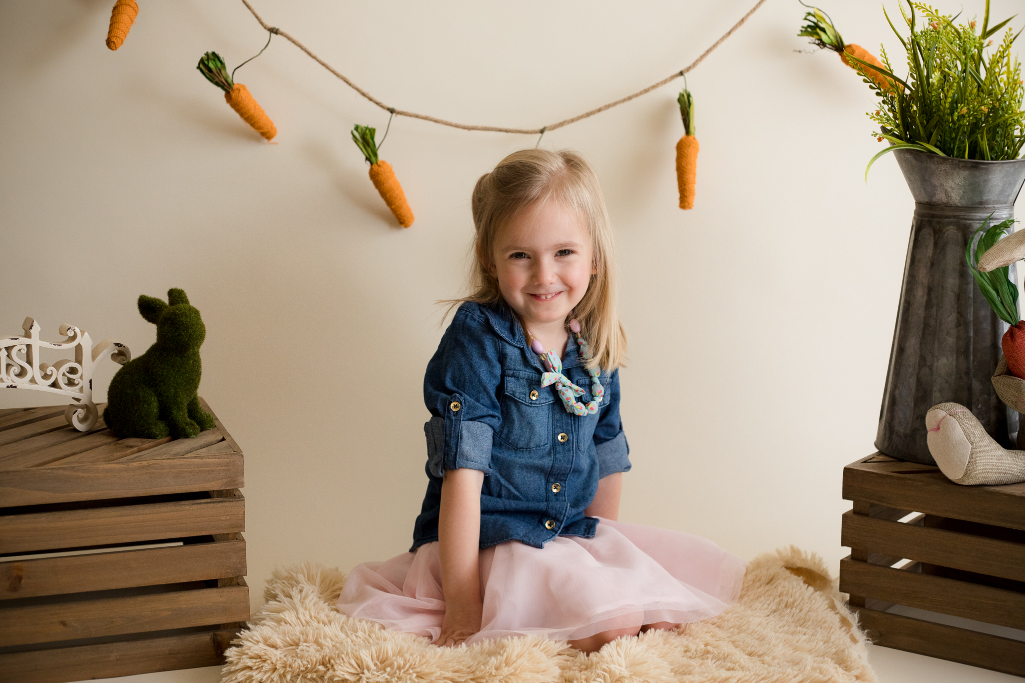 Three year old girl sitting for photo during Easter Mini Session in Cedar Rapids, Iowa.