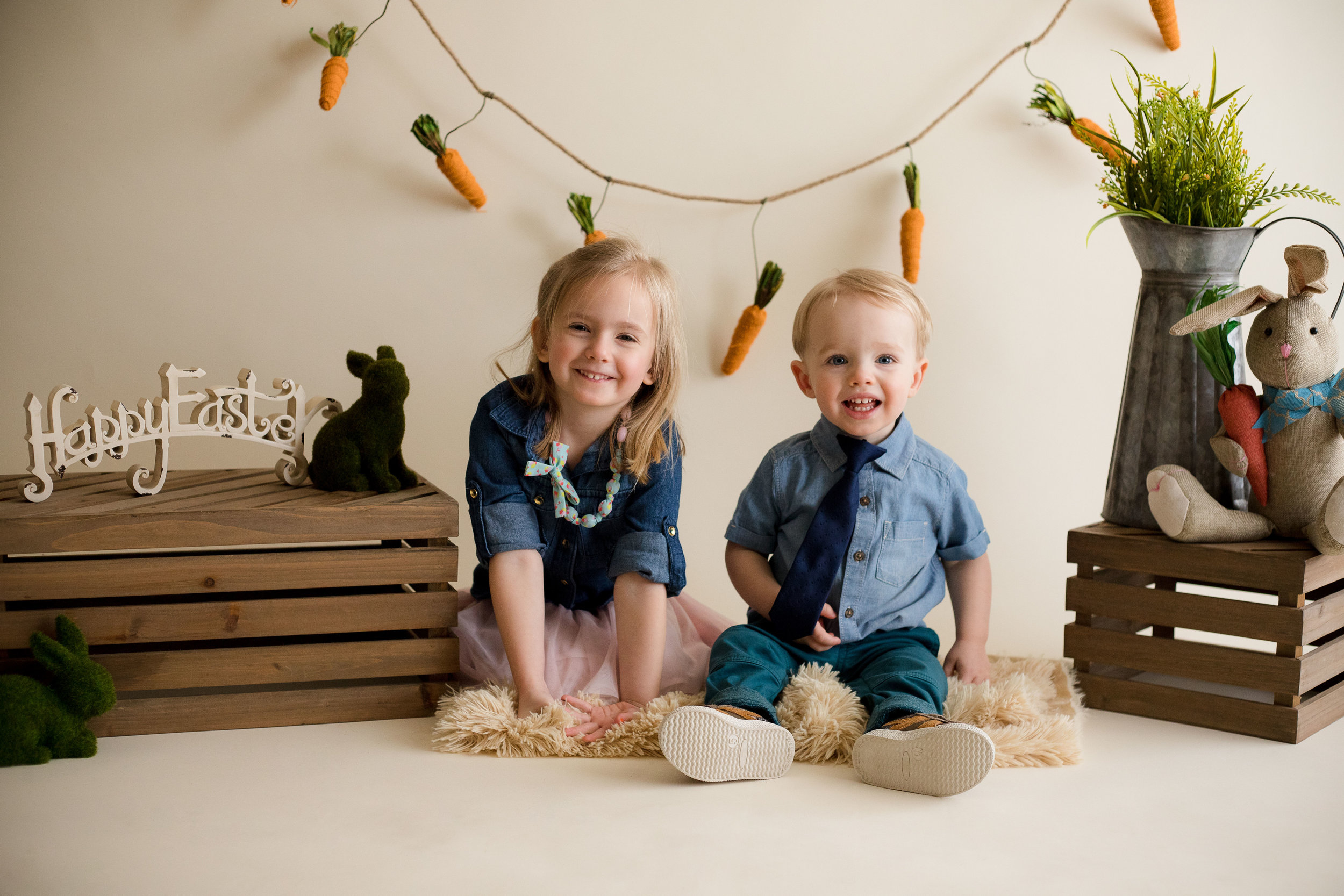 Brother and sister sitting and smiling for camera during in studio Easter Mini Session.