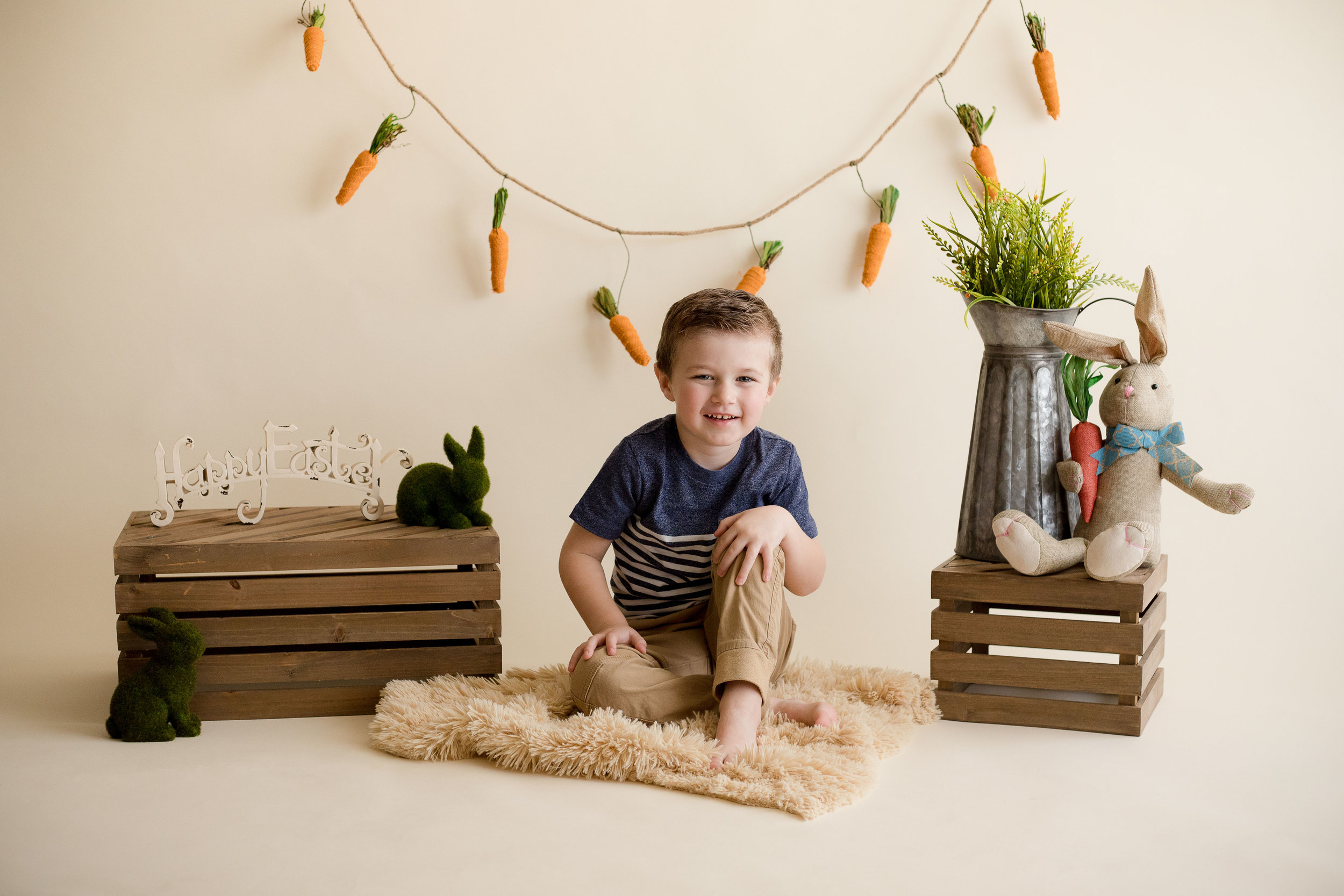 Five year old boy sitting and smiling for a photo during indoor photo session in Cedar Rapids.