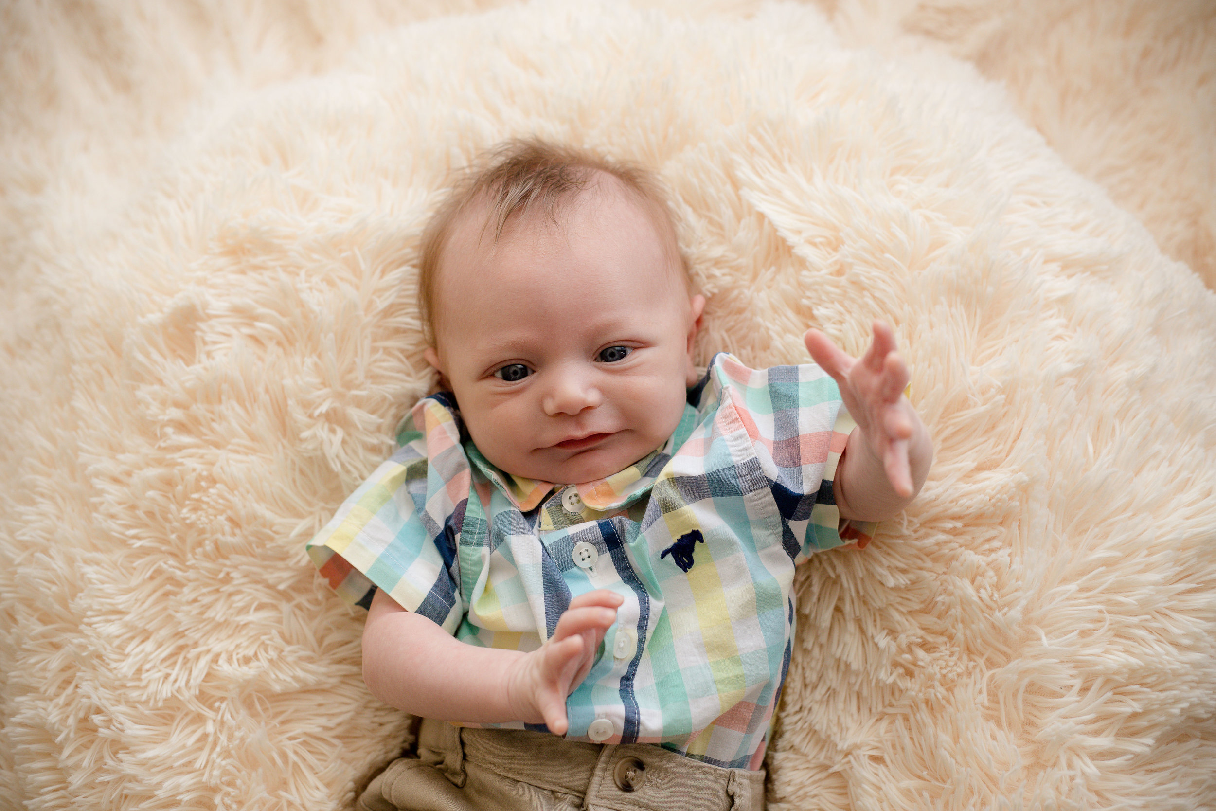 Five week old newborn baby boy laying on blanket and smiling at camera during indoor photo session.
