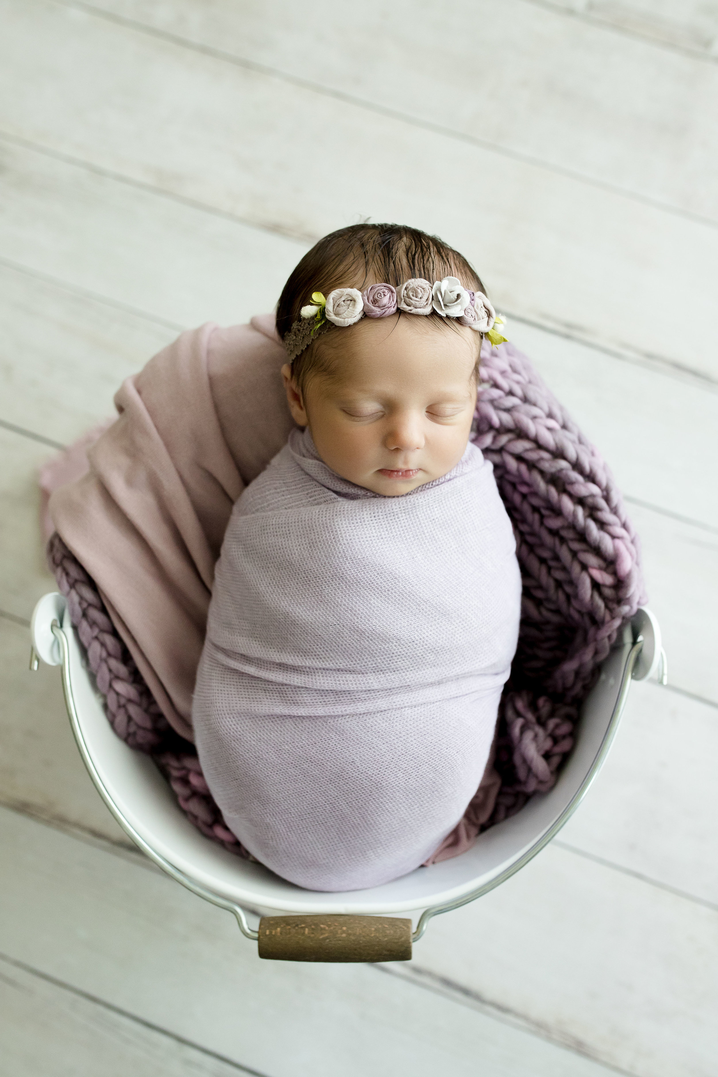 Baby girl sleeping in bucket at Laura Anne Photography.