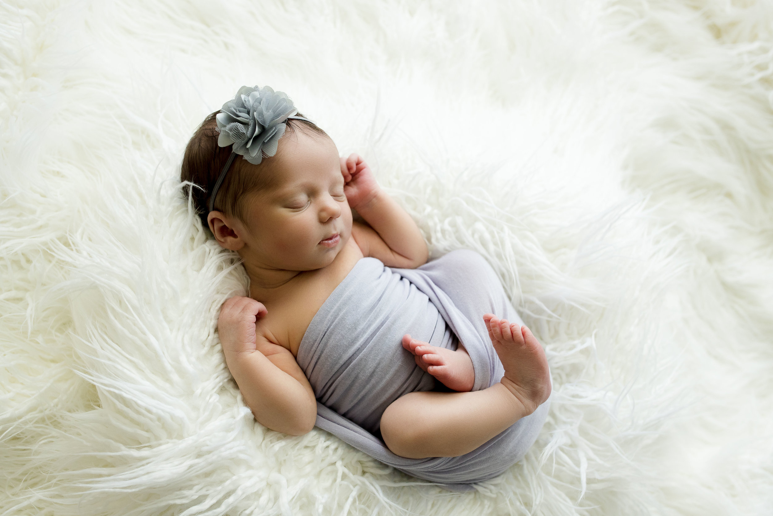 Baby girl swaddled in purple laying on white fur during newborn photo session in Iowa.