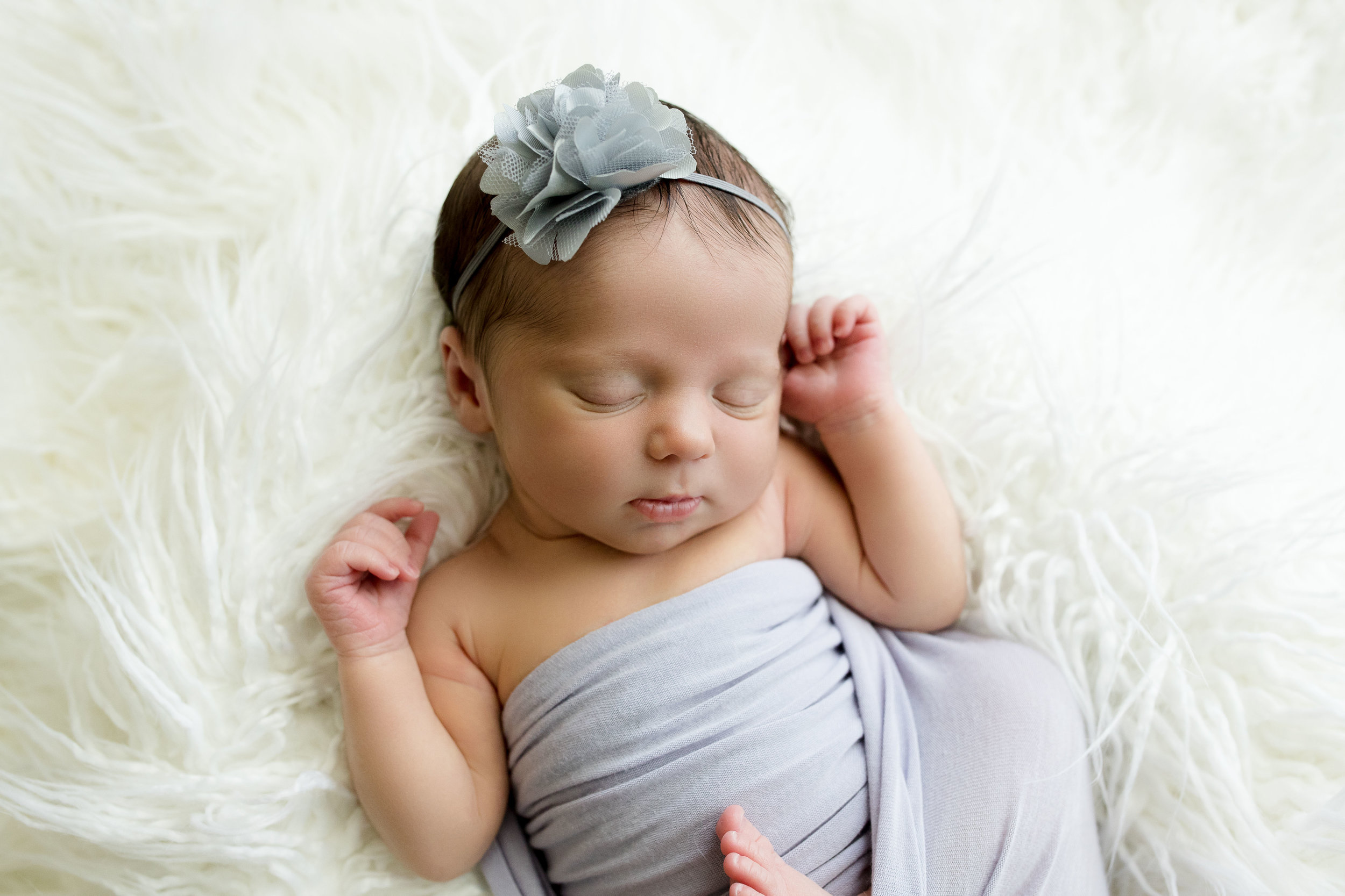 Six day old newborn girl sleeping in white fur with hands up during photo session in Cedar Rapids, Iowa.