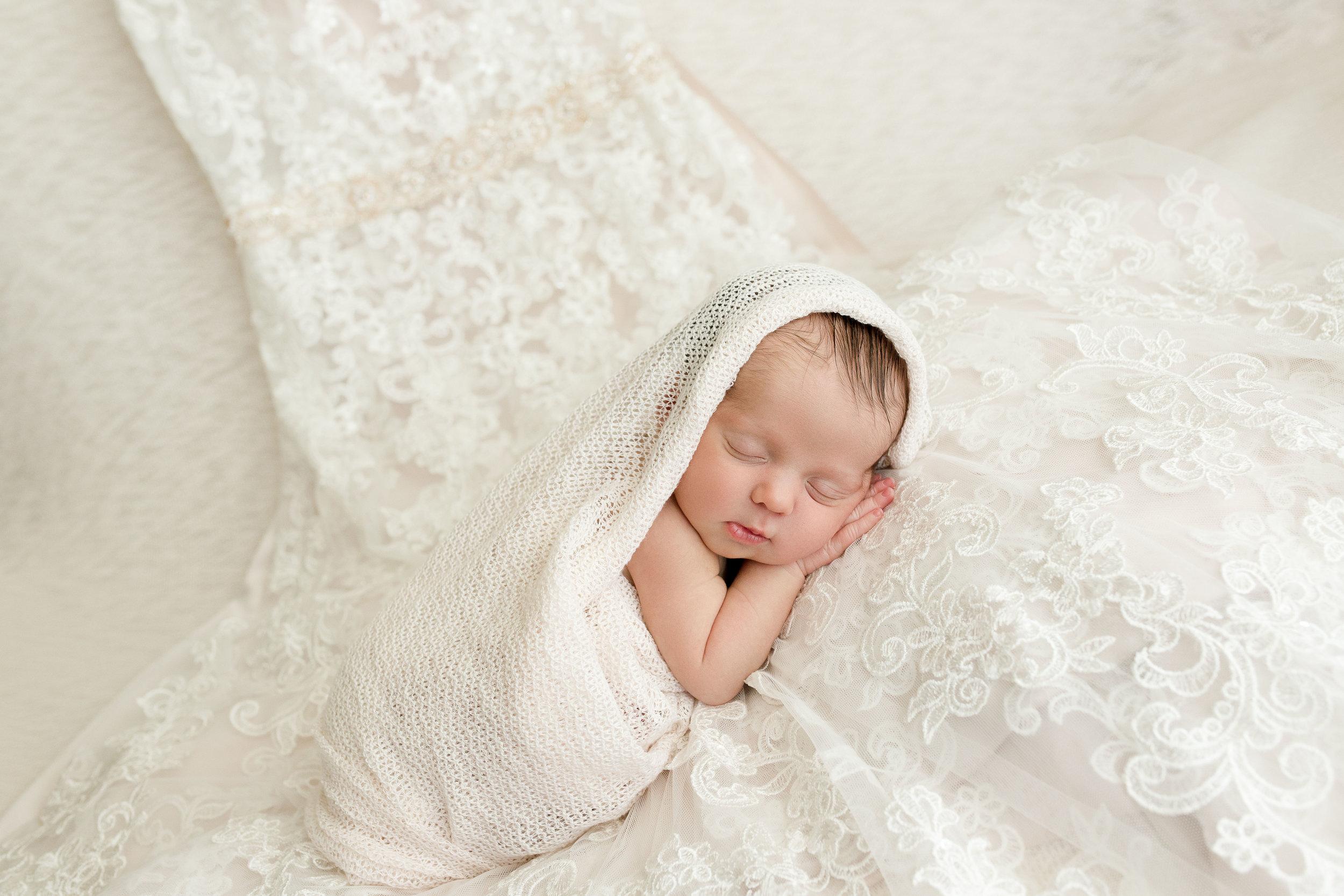 Newborn girl sleeping on mother's wedding dress in Iowa.