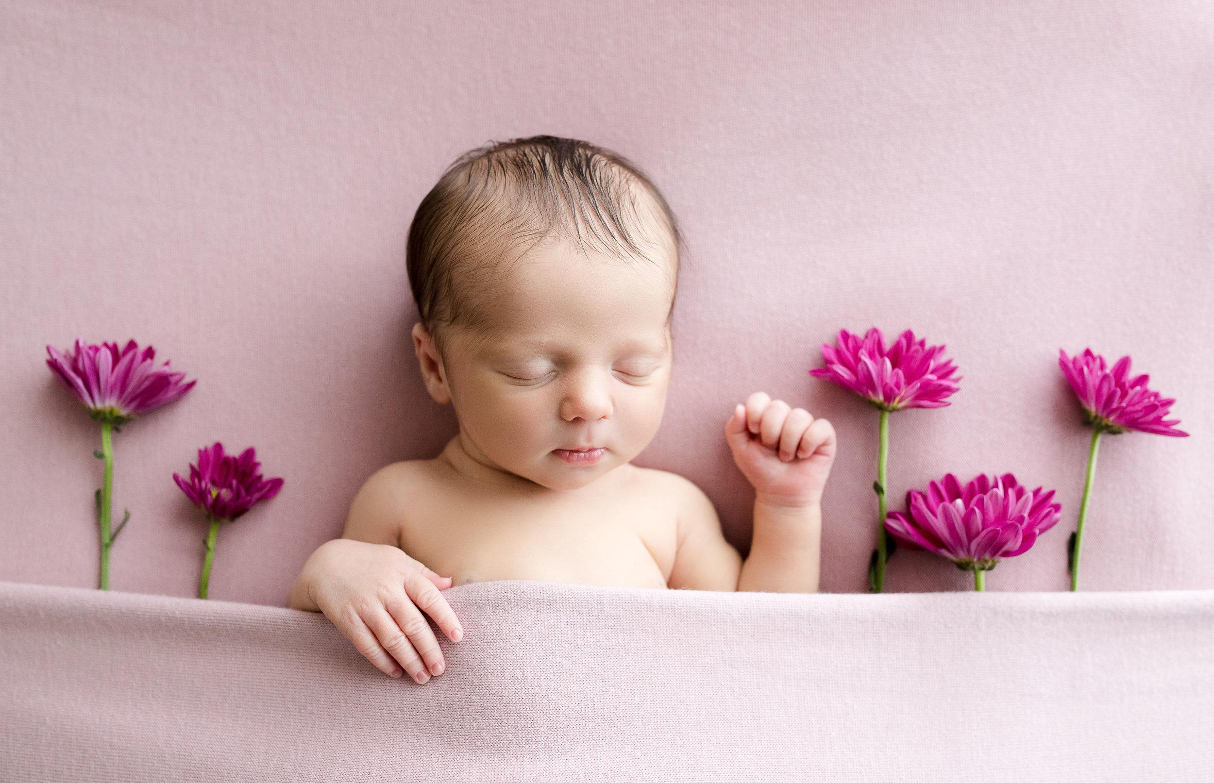 Newborn girl sleeping under blankets near pink flowers during photo session in Cedar Rapids, Iowa.