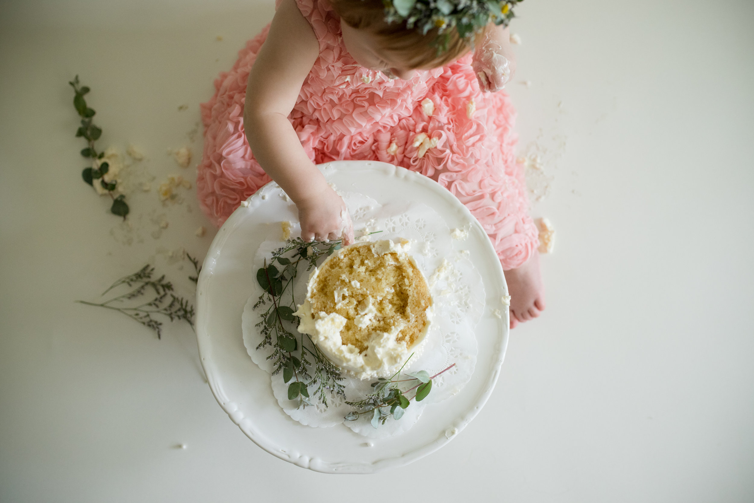 Girl in dress sitting down while eating cake during cake smash photo session on the southwest side of Cedar Rapids, Iowa.