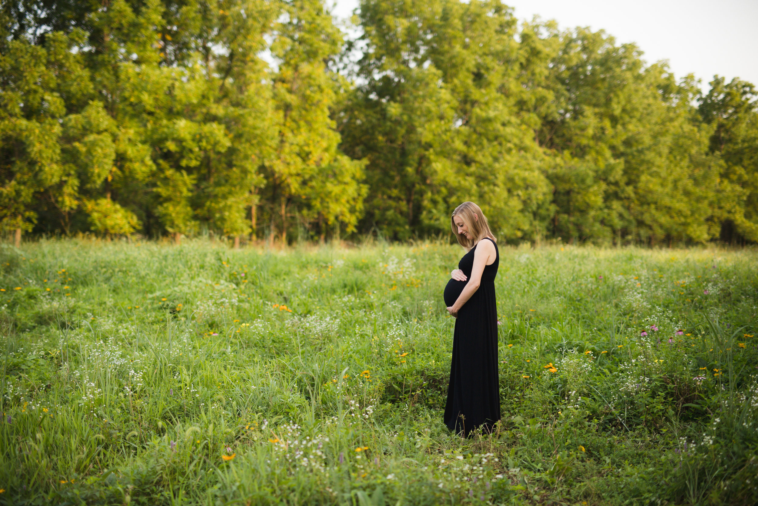 Mother-to-be with twins at 30 weeks standing in a field at Squaw Creek Park in Marion, Iowa.