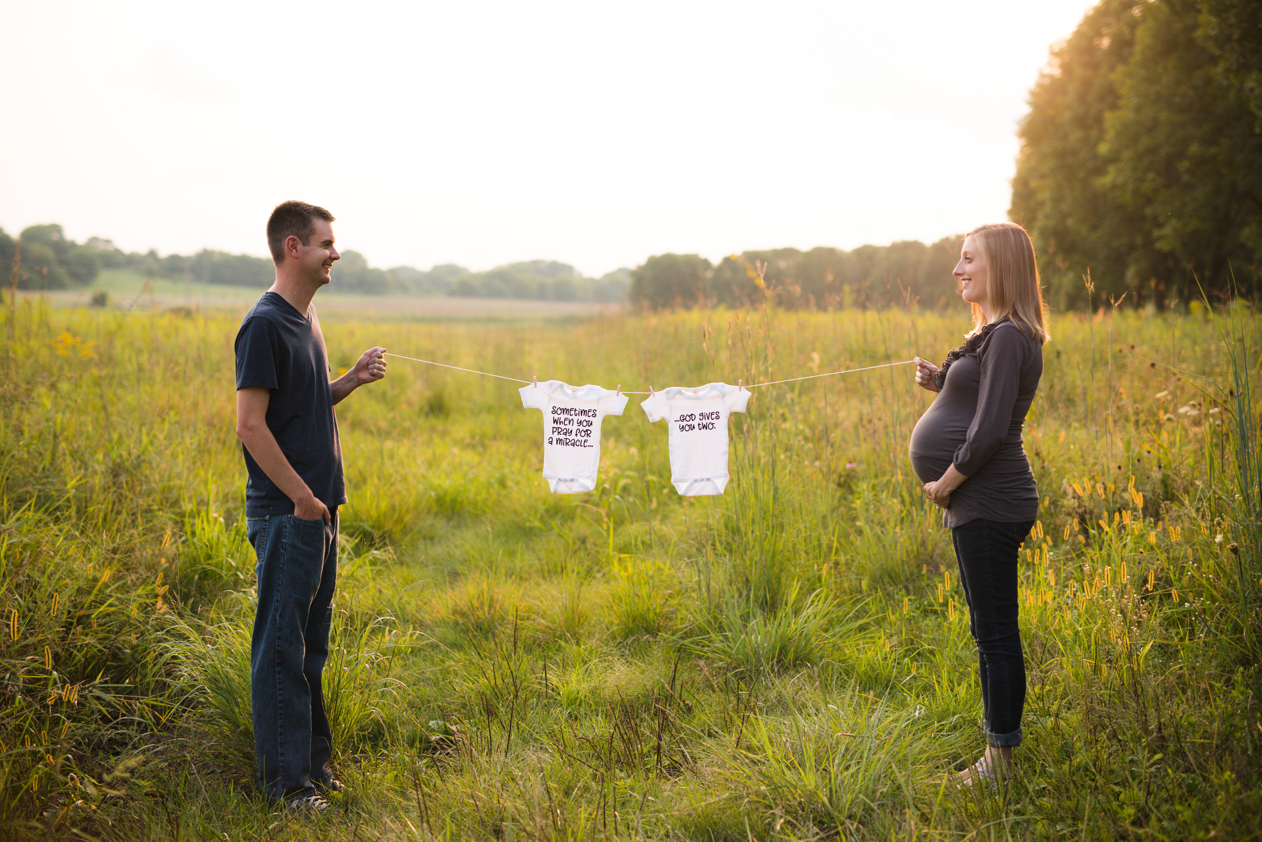 Couple standing holding string with two onesies for twins during maternity photo session at 30 weeks in Cedar Rapids, Iowa.