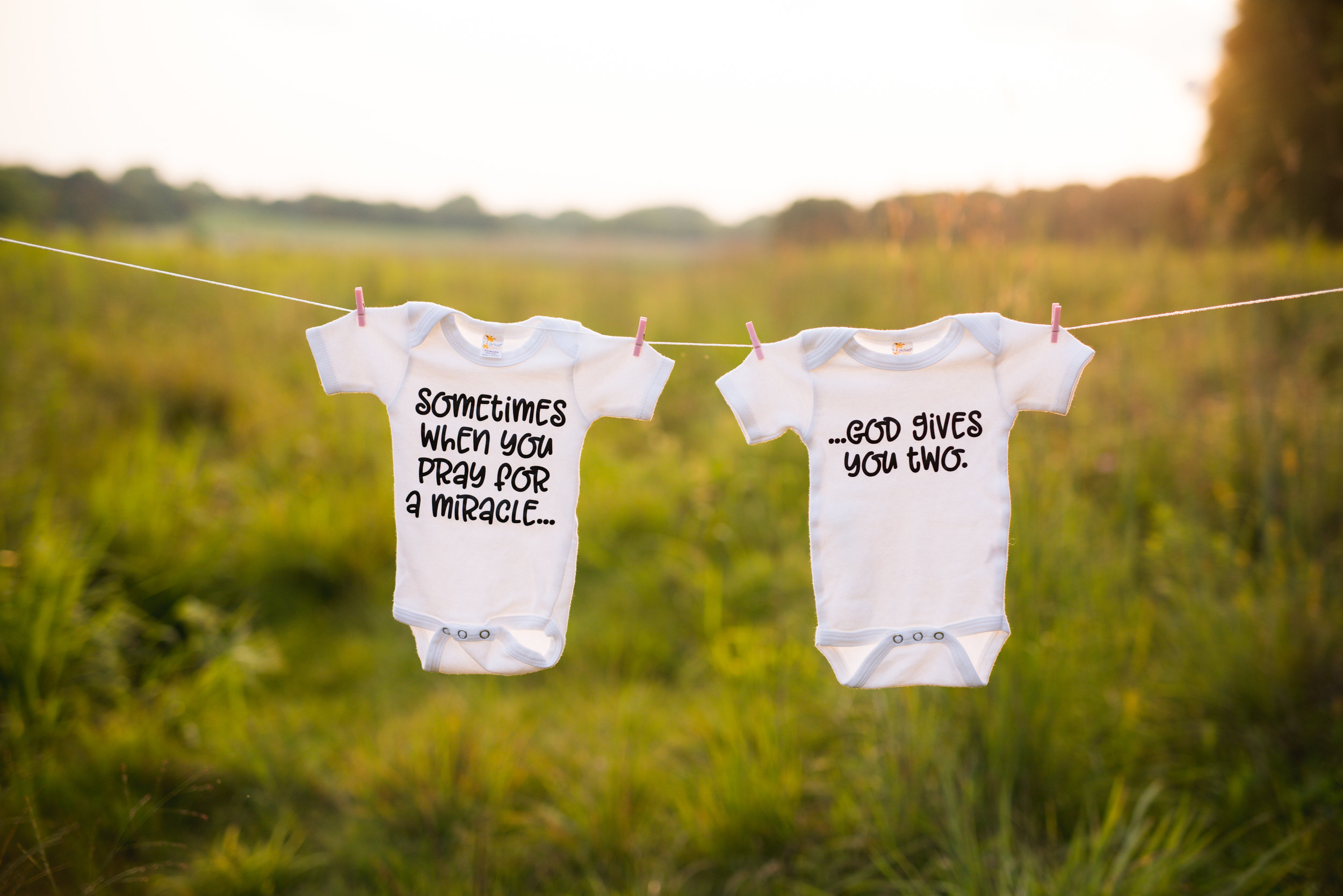 Two twin onesies tied to a string during a maternity photo session at Squaw Creek Park in Marion.