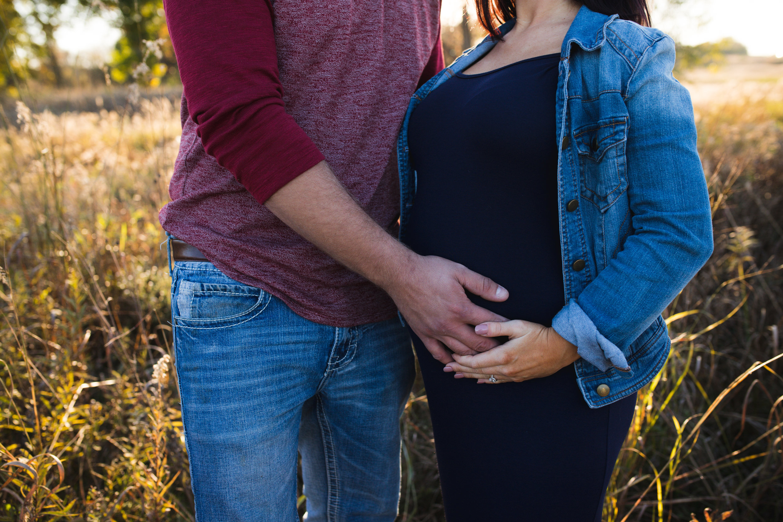 A couple who are 32 weeks pregnant standing side by side holding hands on top of pregnant belly during a maternity photo session in Iowa.