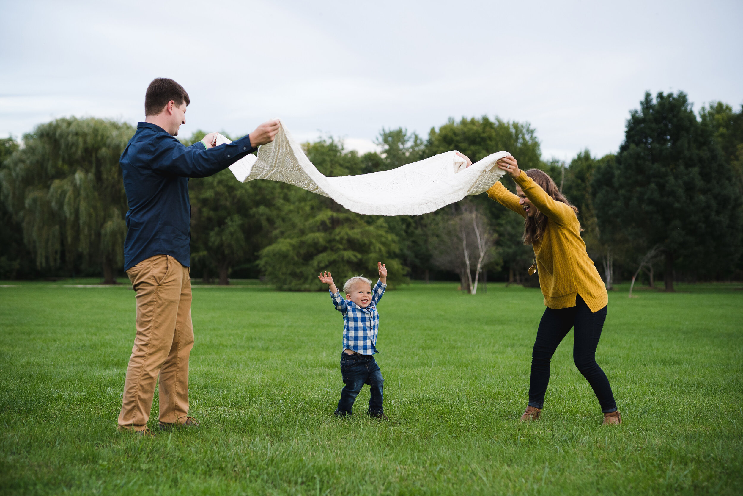 A family of three playing in a park during a fall photo session in Cedar Rapids, Iowa.