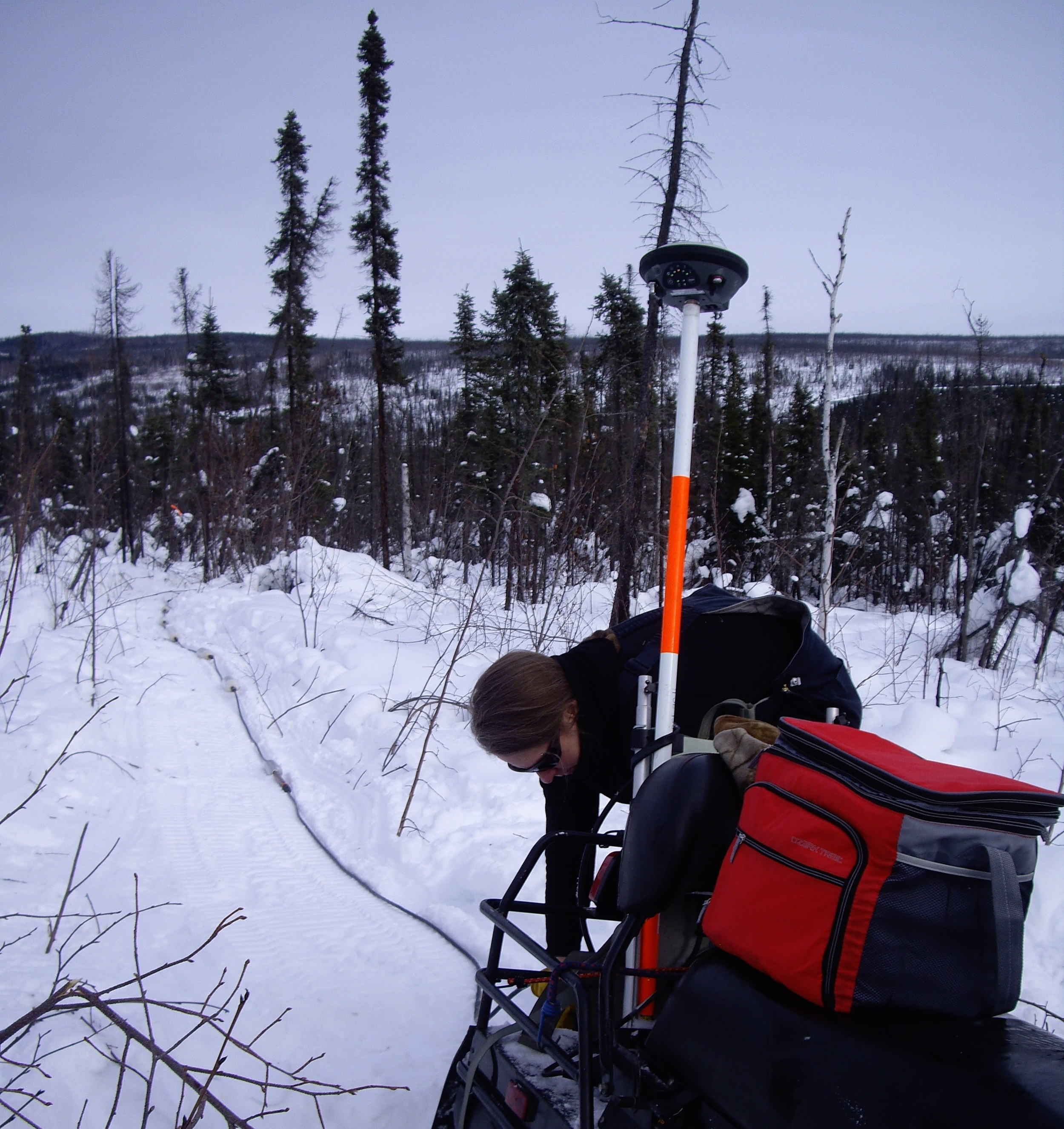 Setting up a GNSS antenna for a resistivity survey along the Dalton highway in Northern Alaska