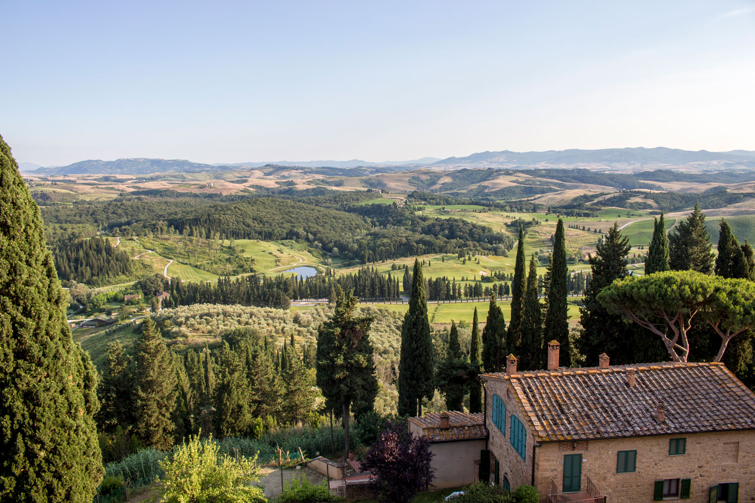 A view of Tuscany, overlooking rolling hills, winding roads and centuries-old vineyards as the warm sun shines down on Castelfalfi, Italy.