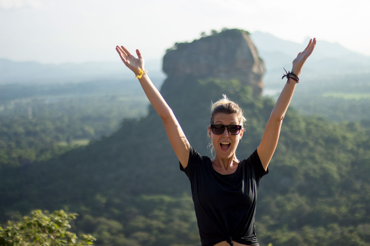 Anne celebrates reaching the top of Pidurangala Rock in Sri Lanka, with Sigiriya in the background.