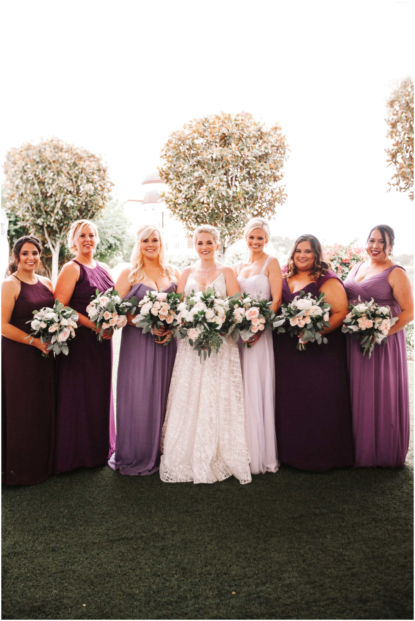 Bride and her bridesmaids holding their white wedding bouquets