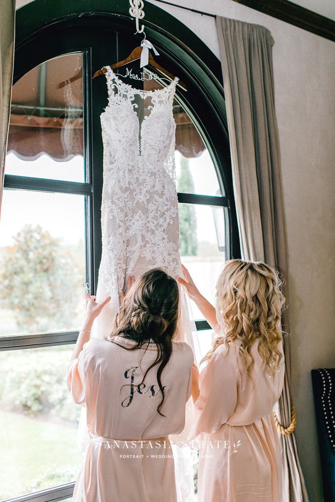 wedding dress hung by the window