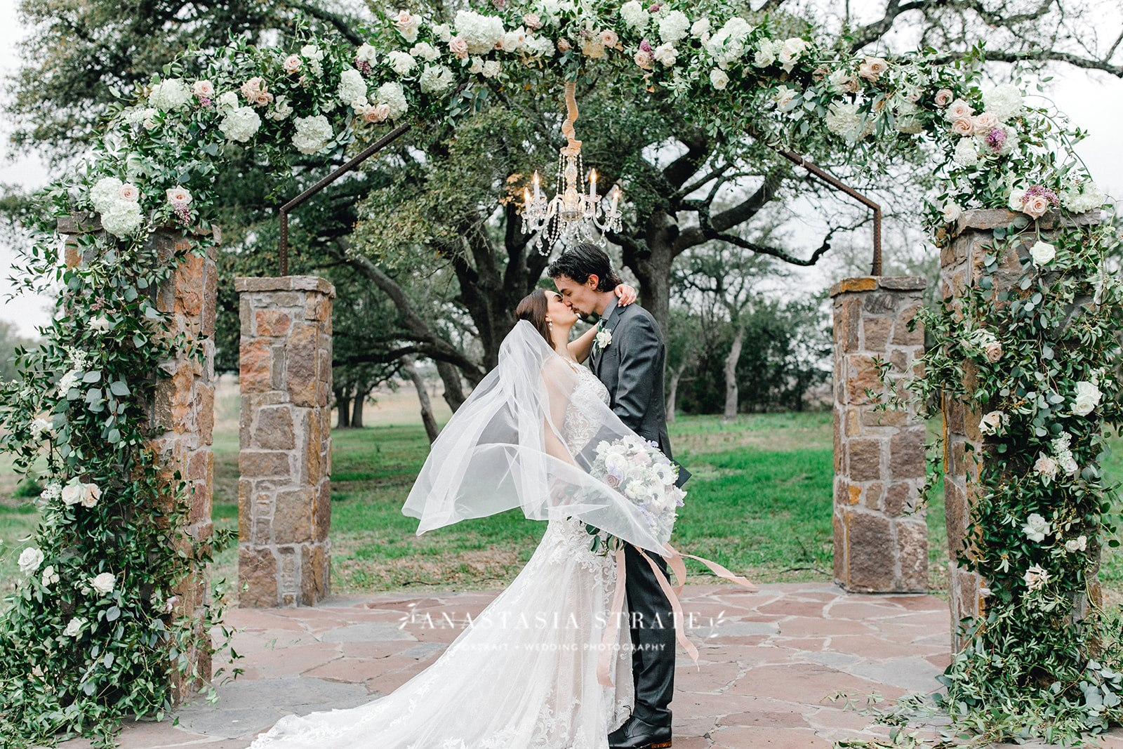 bride and groom kiss under the greenery wedding arch