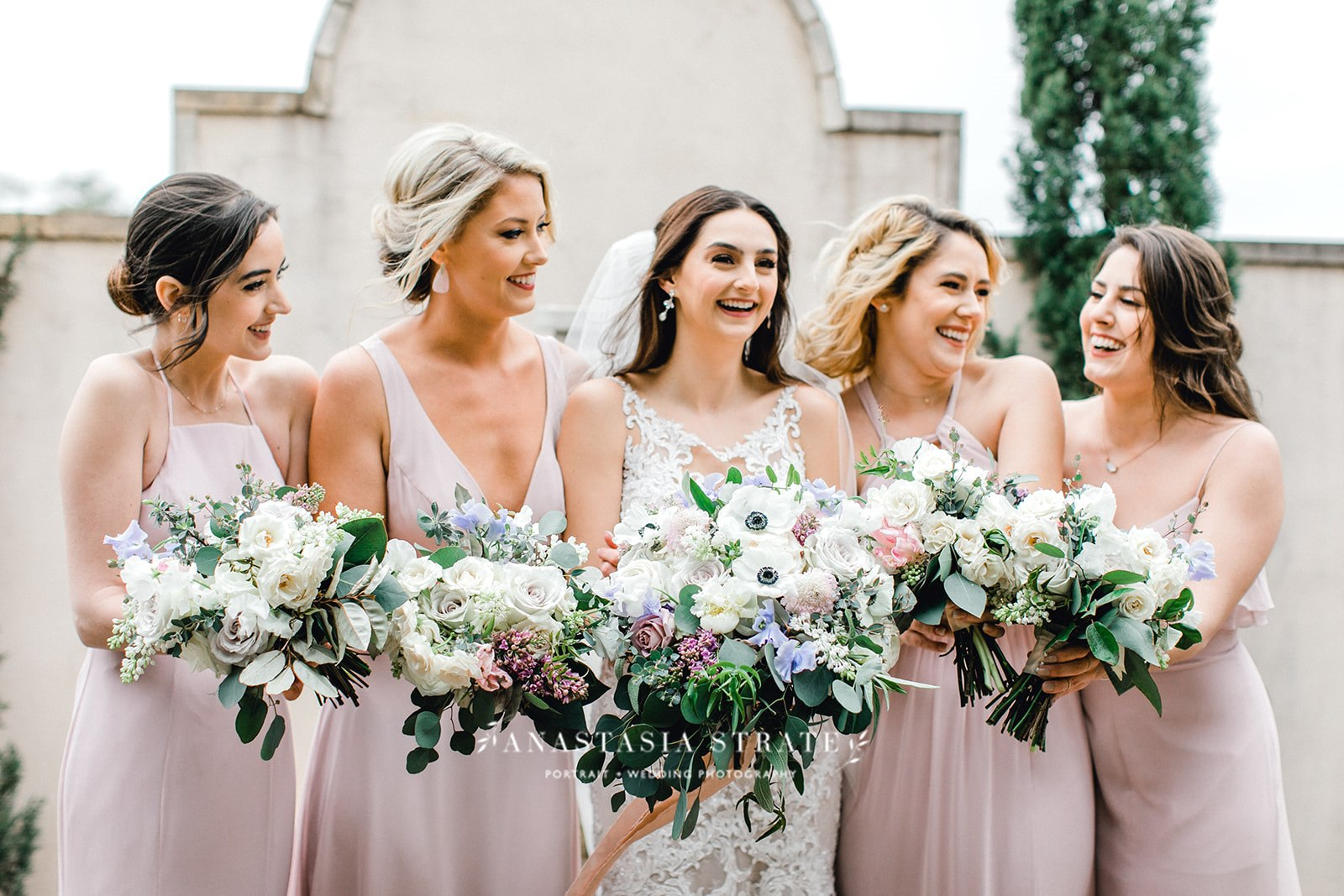 bride and the bridesmaids holding their white wedding bouquets