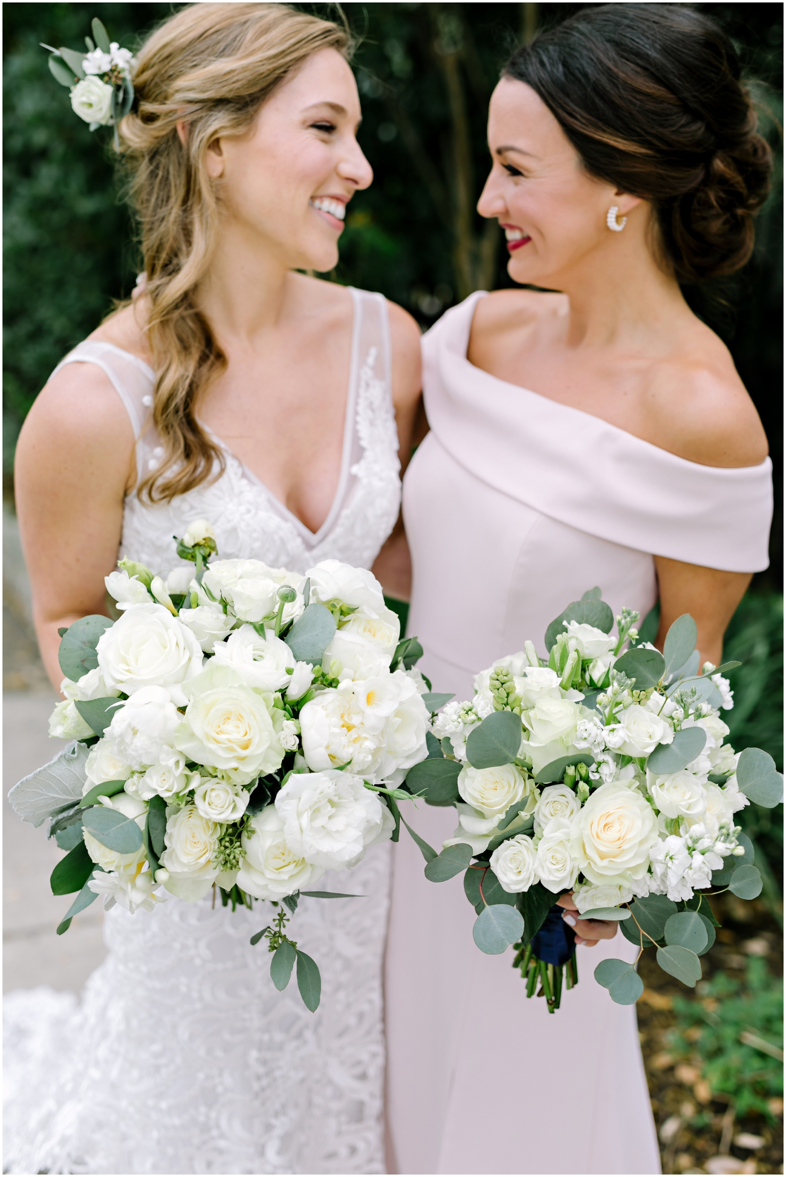 Bride and bridesmaids holding white and greenery wedding bouquet