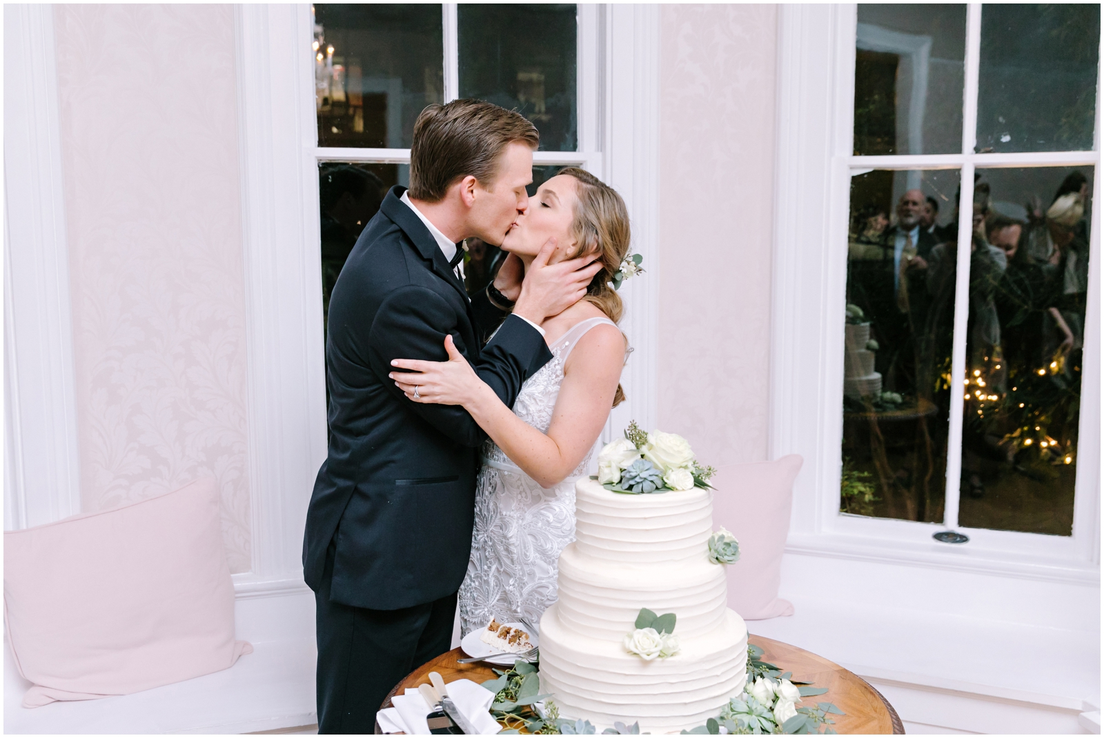 Bride and groom kiss before cutting their wedding cake