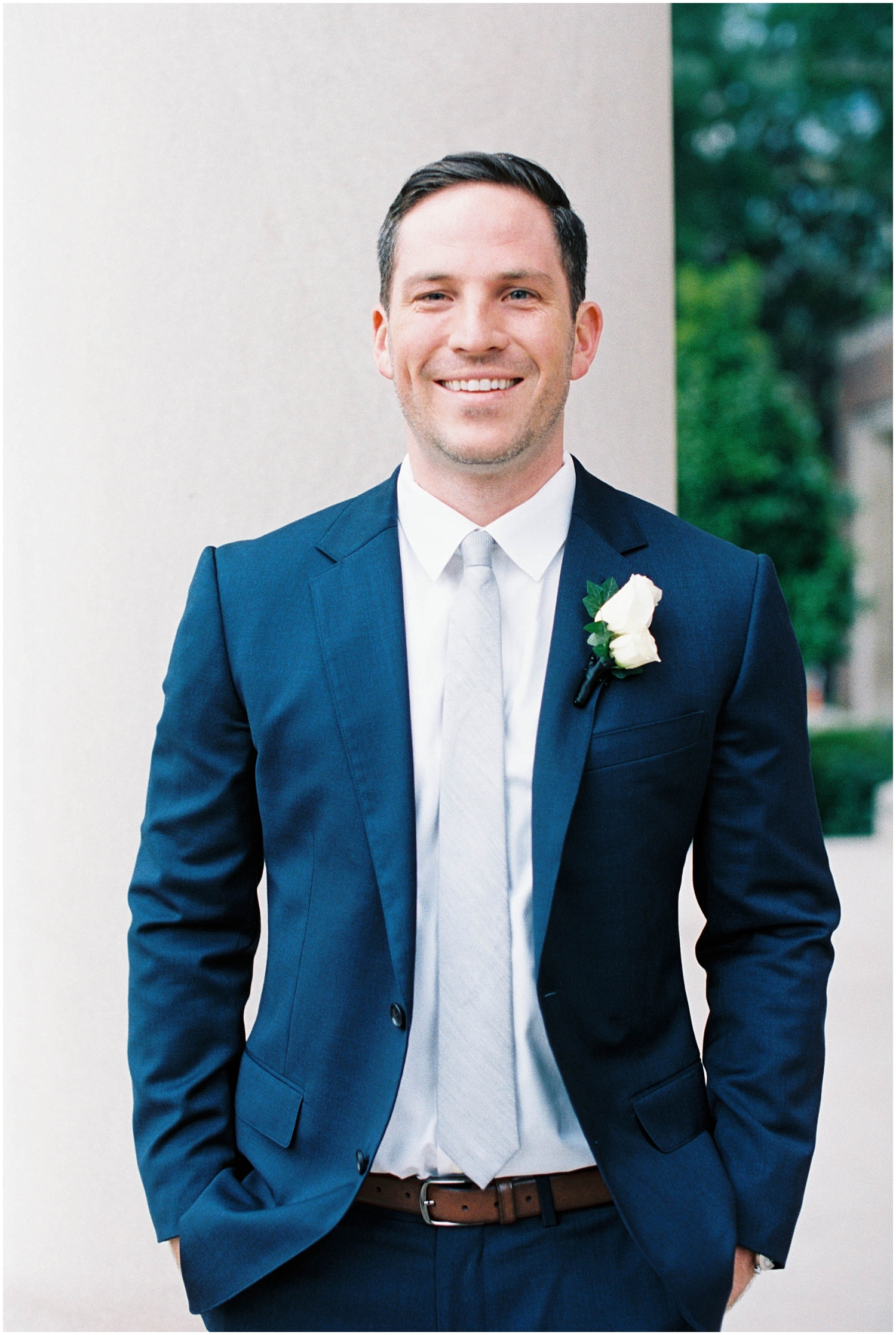 groom wearing a navy suit and boutonniere