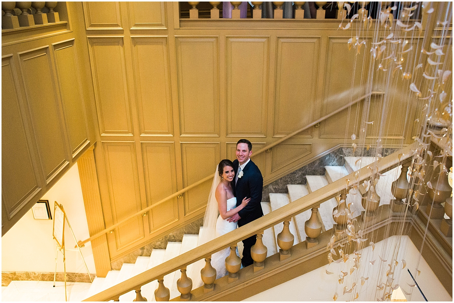 bride and groom standing in a stair well