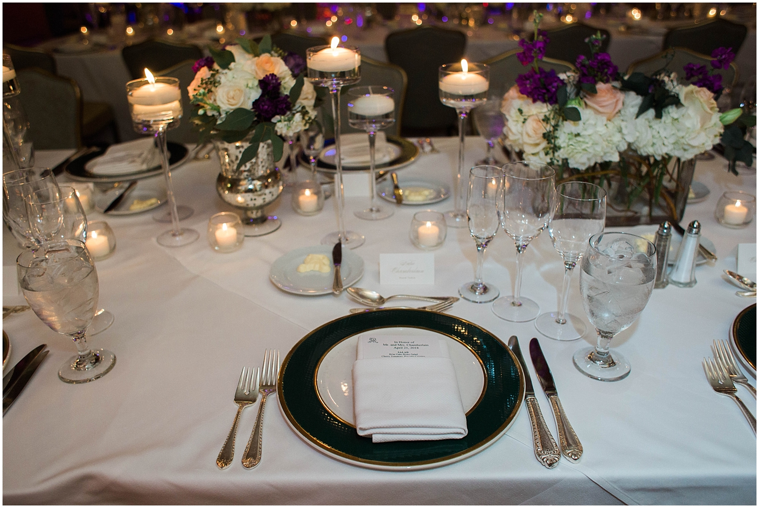 wedding reception table setting with candles and floral decor