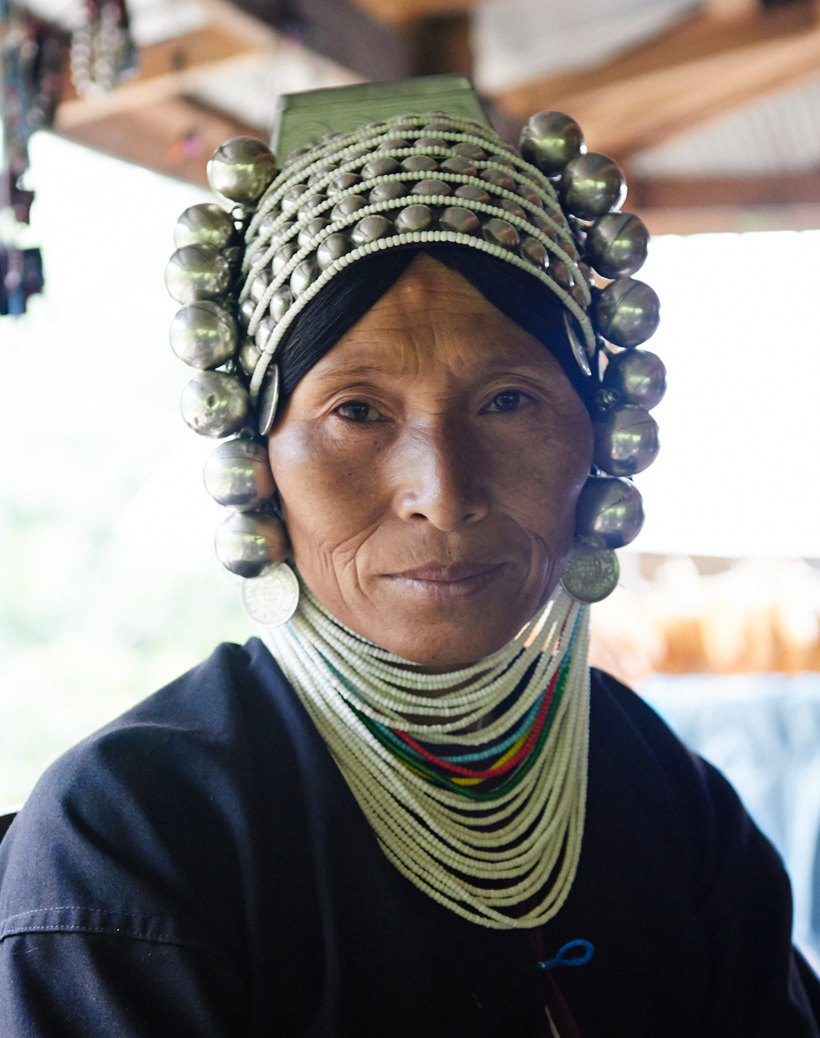 Custom. - An Akha woman wearing her headdress of silver,shells and beads.