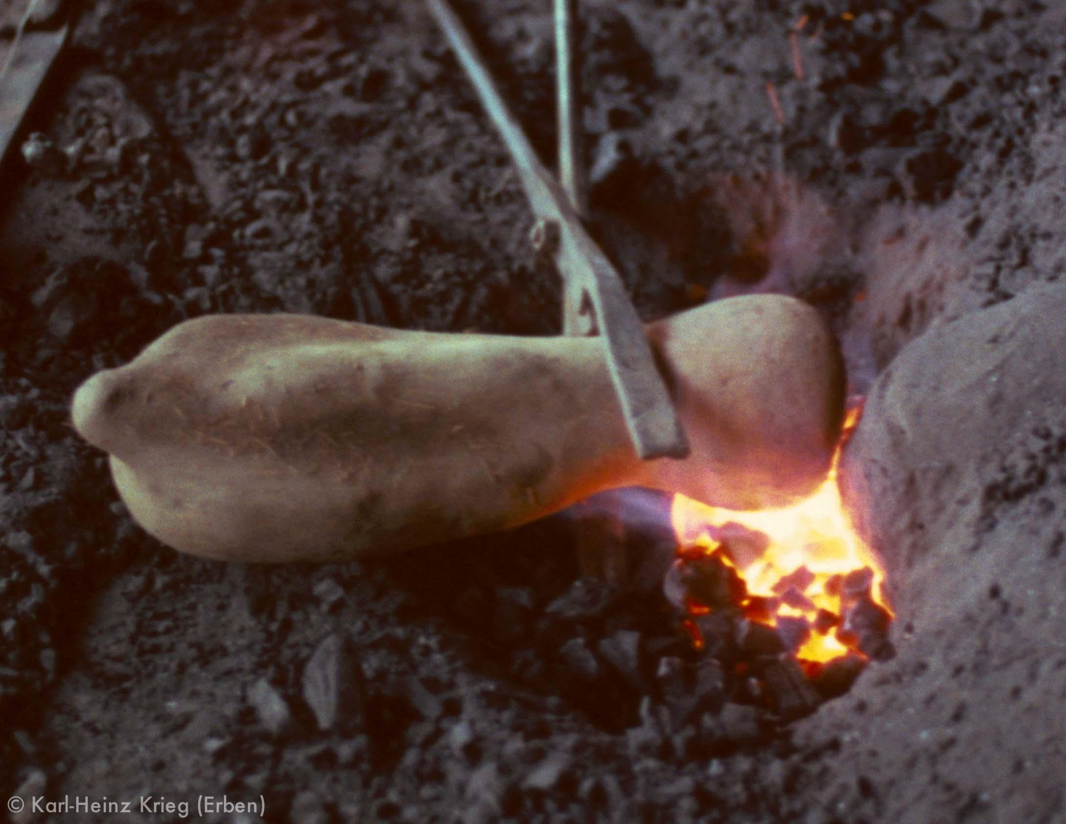 Herstellung einer Gussform für eine Bronzemaske. Der Lehmmantel, in dem sich ein Maskenmodell aus Wachs befindet, wird erhitzt. Foto: Karl-Heinz Krieg, Gbon (Region von Boundiali, Côte d'Ivoire), 1978