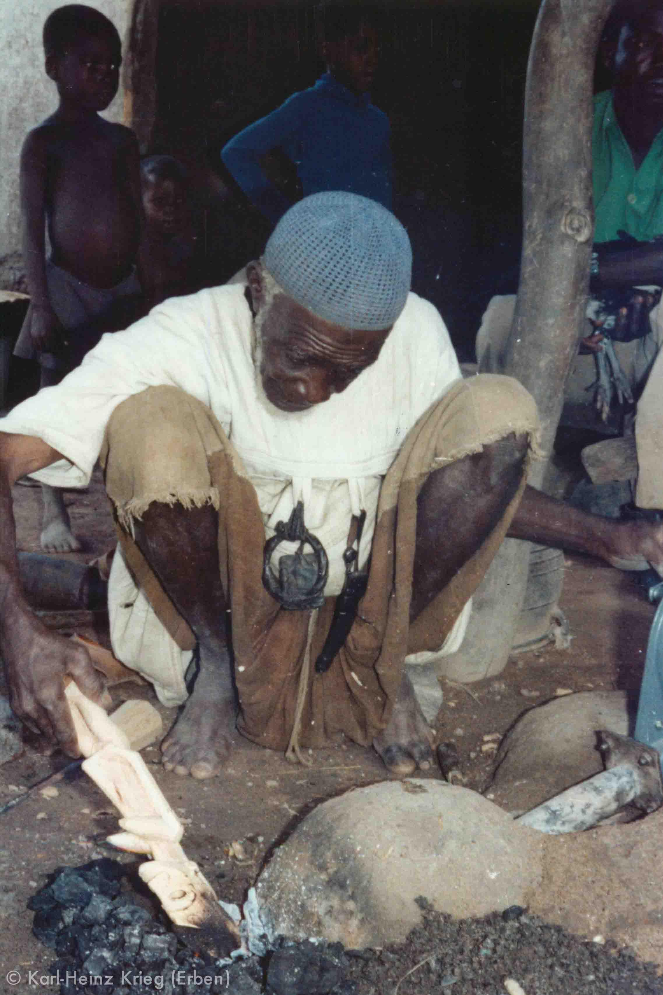 Tinnin Fané blackens the carved figure on an open fire at the forge. Photo: Karl-Heinz Krieg, Fakola (Mali), 1981