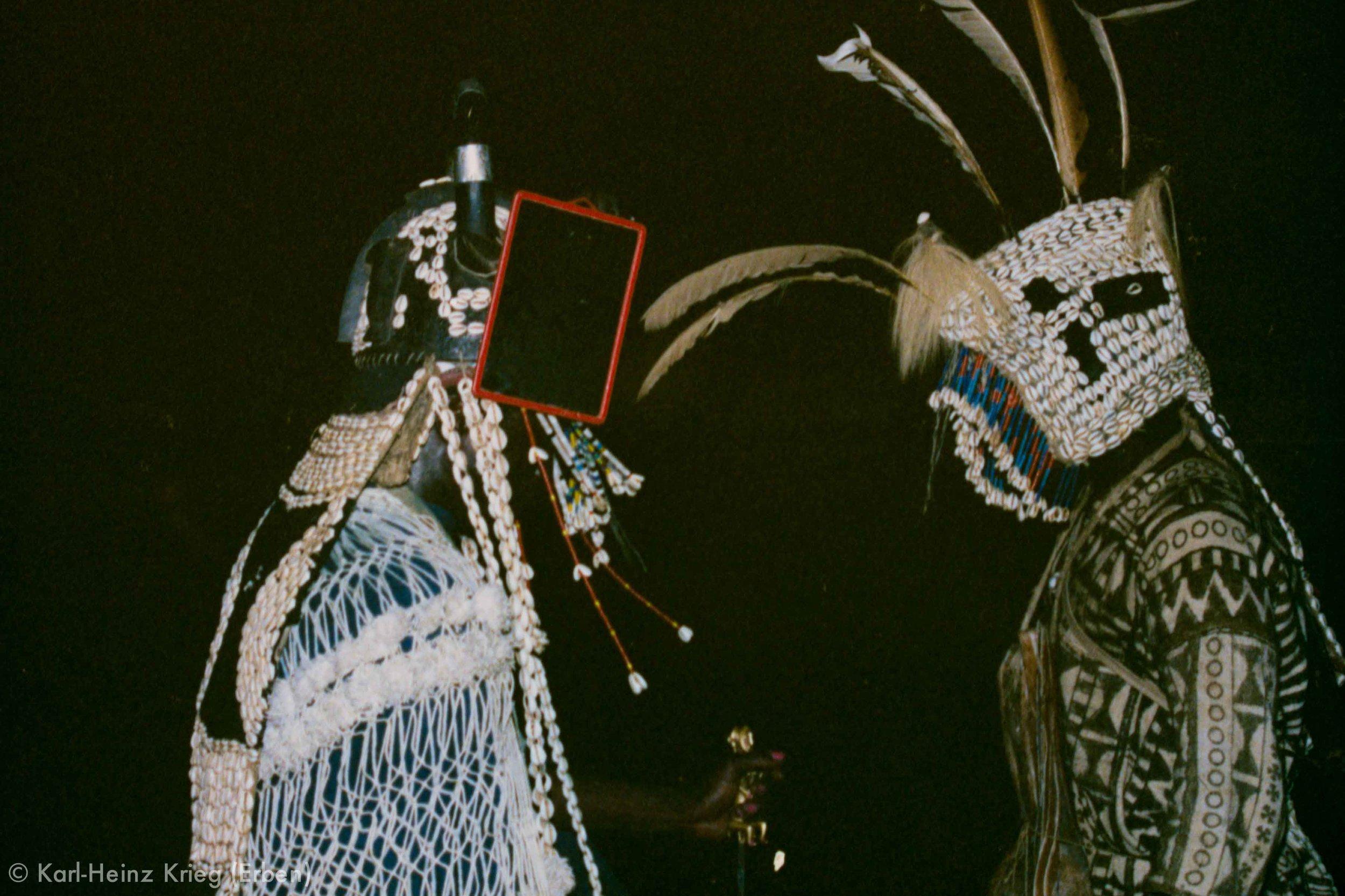 Niyuo -Sänger mit  Dagu -Helm und Stab (links) und  Niyuo -Tänzer mit Haube (rechts). Foto: Karl-Heinz Krieg, Kapyala (Region von Boundiali, Côte d'Ivoire), 1980