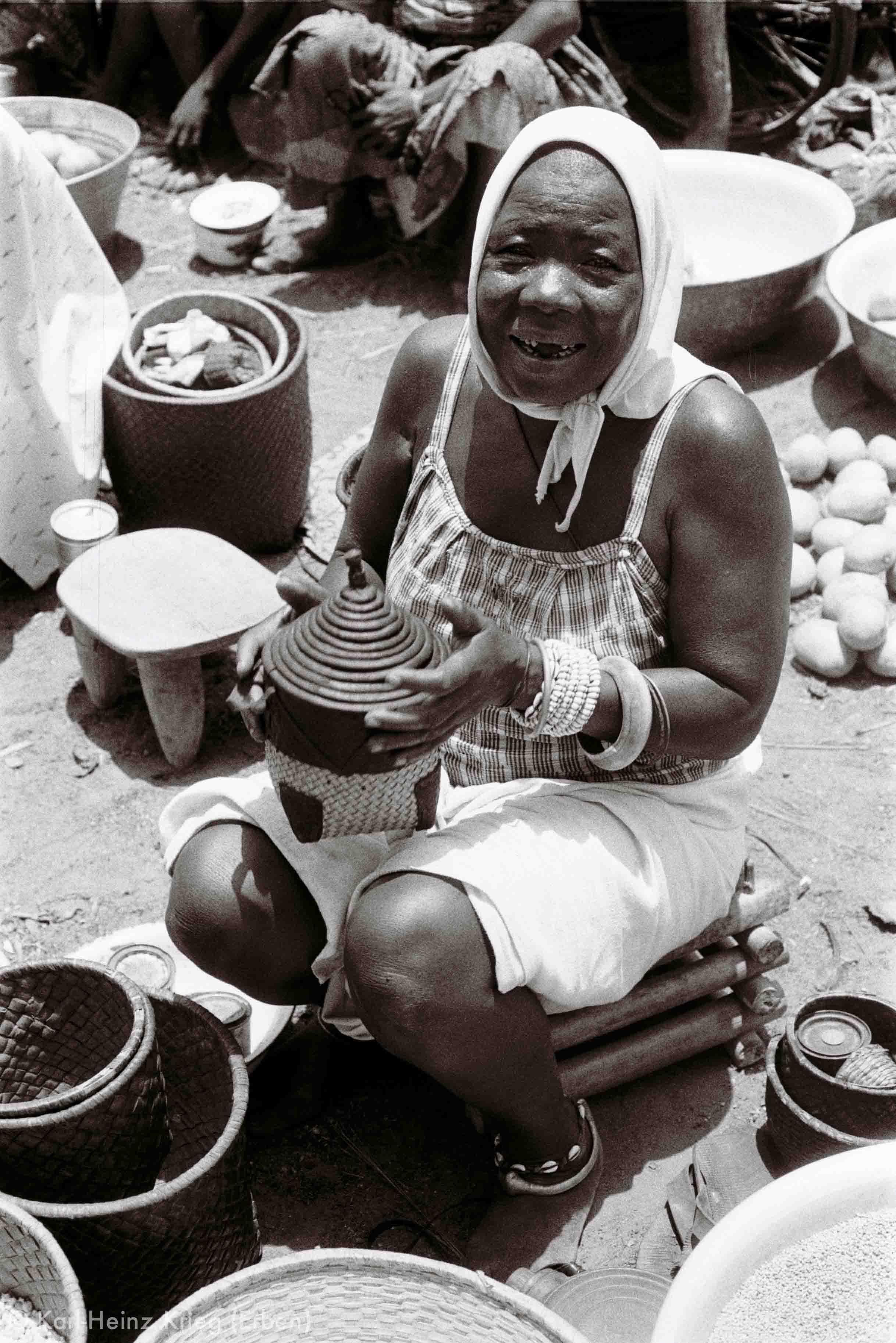 Gué-Frau mit Messkörbchen und traditionellem Schmuck (Bronze-Fußreif, Elfenbein-Armreif und Schmuck aus Kauris). Foto: Karl-Heinz Krieg, Gouindougouba (Region von Banfora, Burkina Faso), 1980