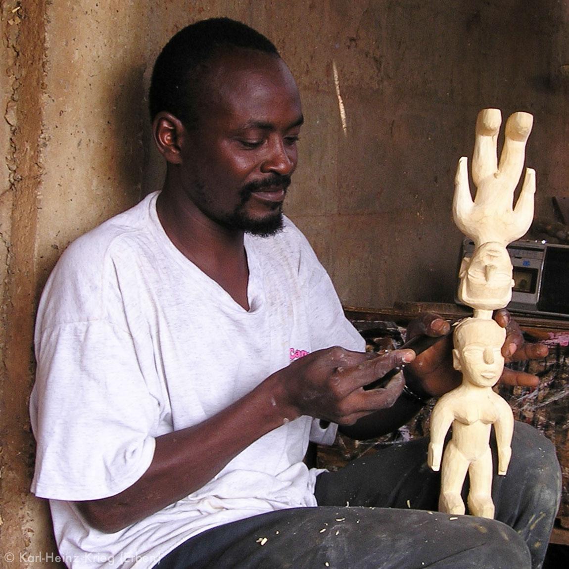 Voodoo-Schnitzer Koffi Agbédégpé schnitzt ein Figurenpaar in seiner Werkstatt in Lomé. Er schnitzt zwei Figuren an einem Stück, um sie später in der Mitte zu trennen. Foto: Helen Krieg, Lomé, 2004
