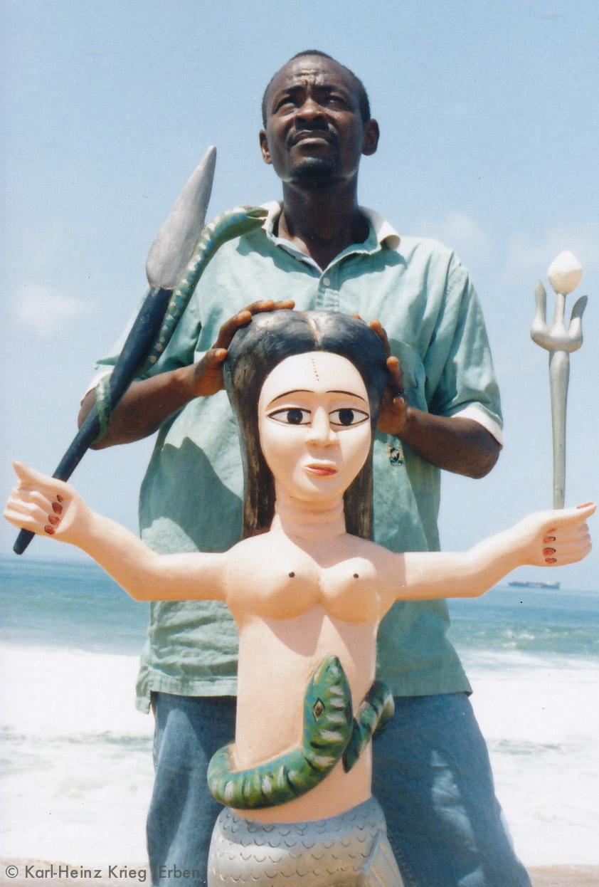 Voodoo-Schnitzer Koffi Agbédégpé mit einer von ihm geschnitzten Mamy Wata-Figur. Foto: Karl-Heinz Krieg