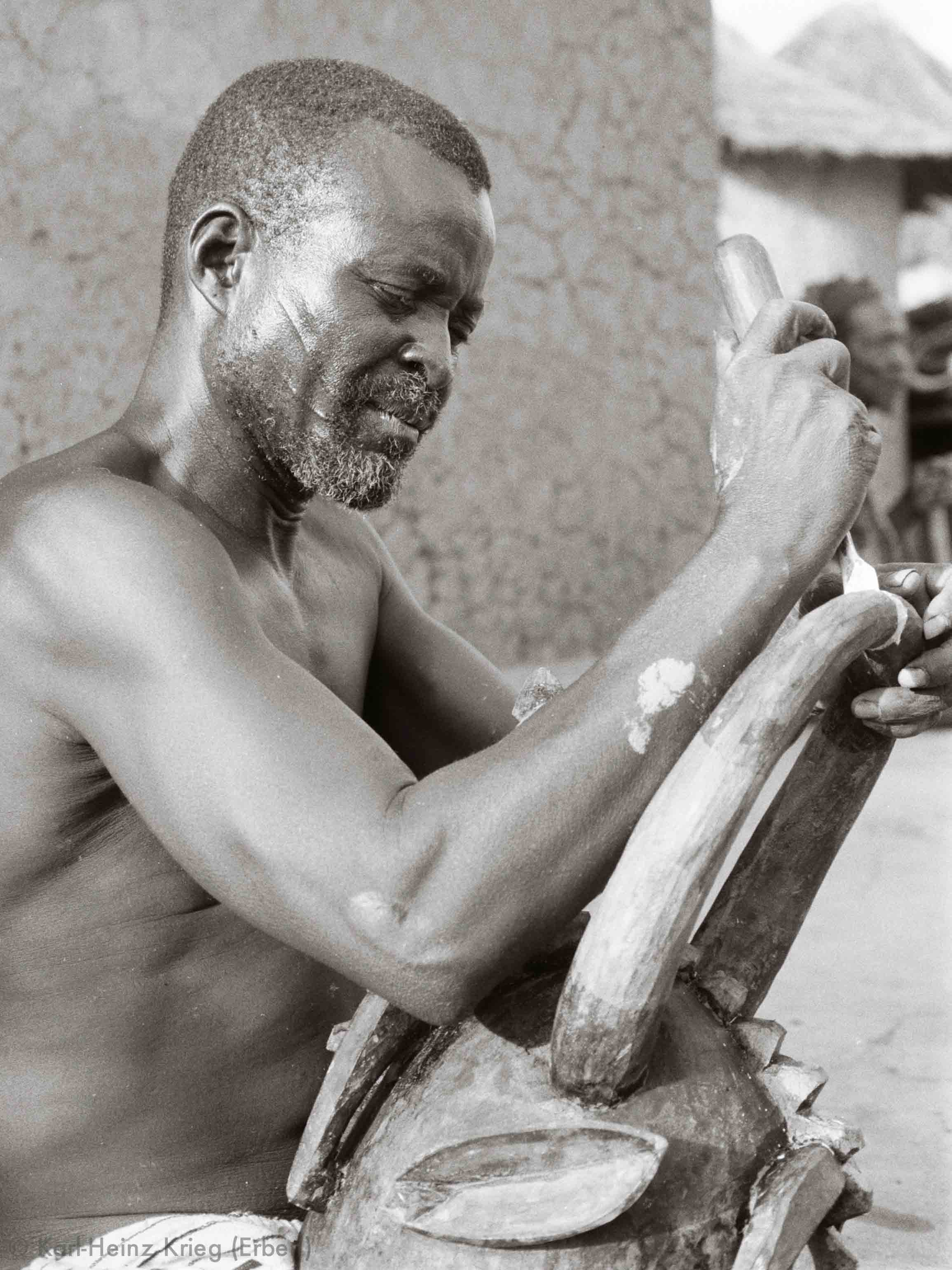 Karna Ouattara carving a helmet mask in his workplace. Photo: Karl-Heinz Krieg, Nafoun (Region of Boundiali, Côte d'Ivoire), 1975