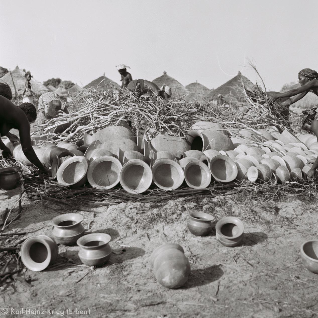 Töpfe werden zum Brennen aufgeschichtet und mit Kleinholz abgedeckt. Foto: Karl-Heinz Krieg, Zekaha (Region von Boundiali, Côte d'Ivoire), 1977