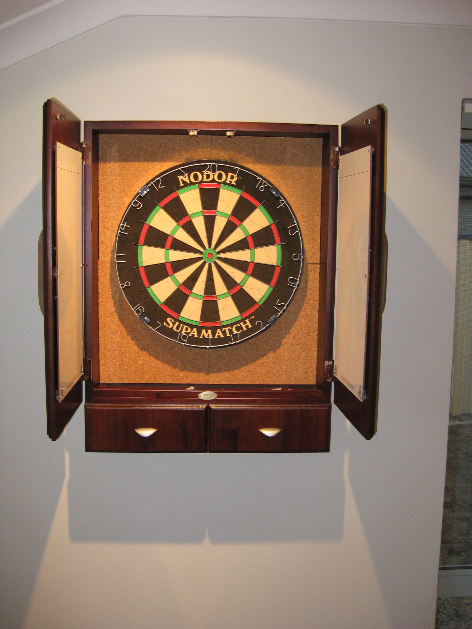 Dartboard cabinet with cork backing, whiteboards in the door and  drop down storage below