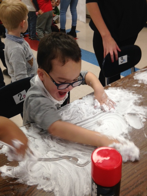Elementary school student has fun playing with flour.