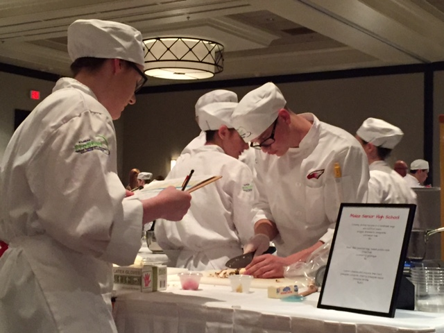 Culinary students reading off instructions for proper dishes.