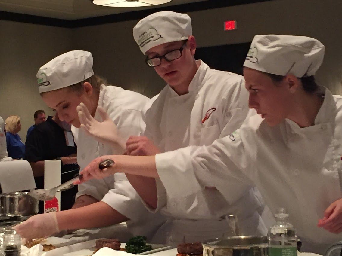 Culinary students working together to perfect a dish
