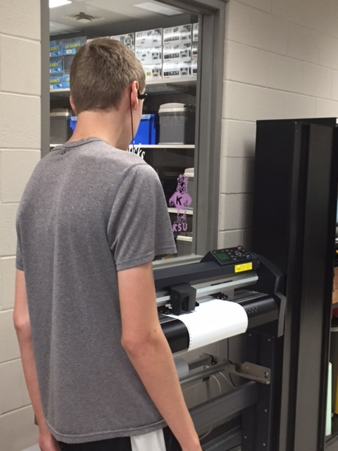 Graphic Design student watches his project finish on a vinyl-cutting printer.