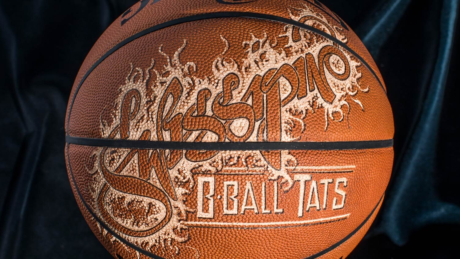 A basketball tattooed, etched and burned in beautiful typography