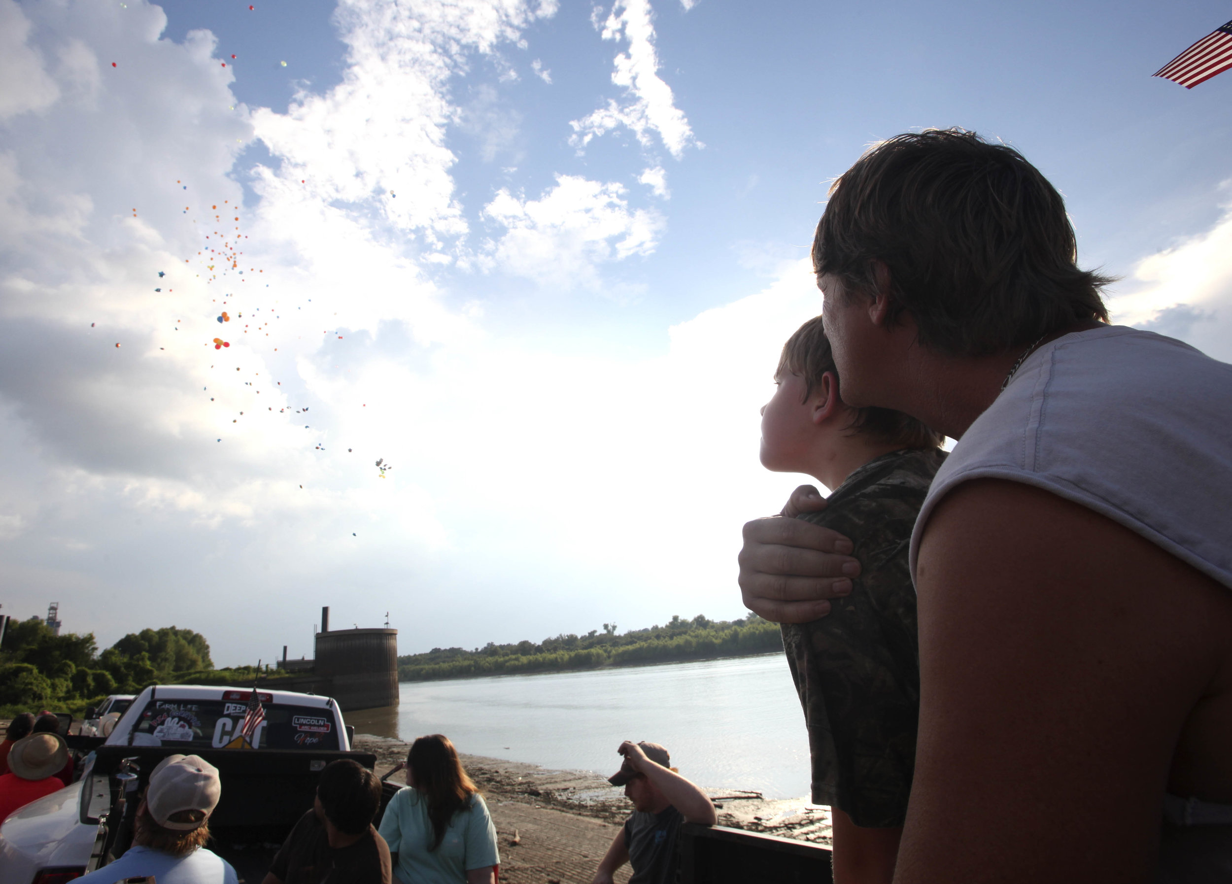 Stan Collins holds Tristan Howell, Michael's younger brother, as balloons float upward  during the balloon release for his son, Michael Collins who was killed when the off-road construction vehicle he was driving rolled into the Mississippi River in 2016, at the Vicksburg Riverfront Wednesday; the anniversary of his death. Collins searched the Mississippi River for 11 days and 10 nights looking for his son. (Courtland Wells/The Vicksburg Post)