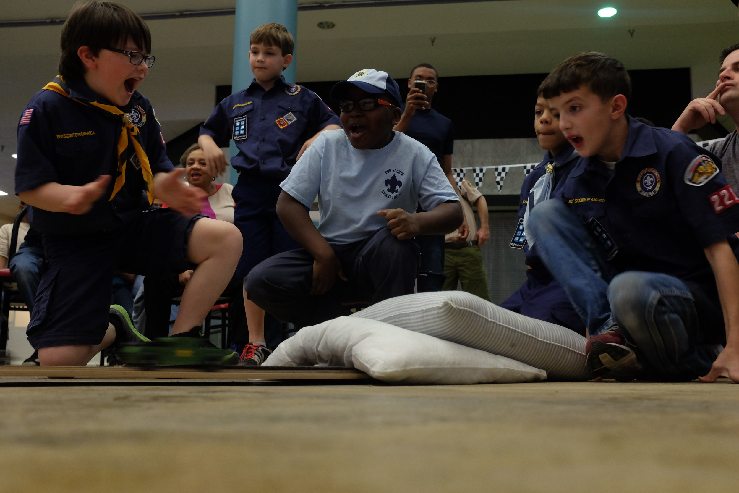 Scouts watch as a pinewood derby cars finish races on the track.  (Courtland Wells/The Vicksburg Post)