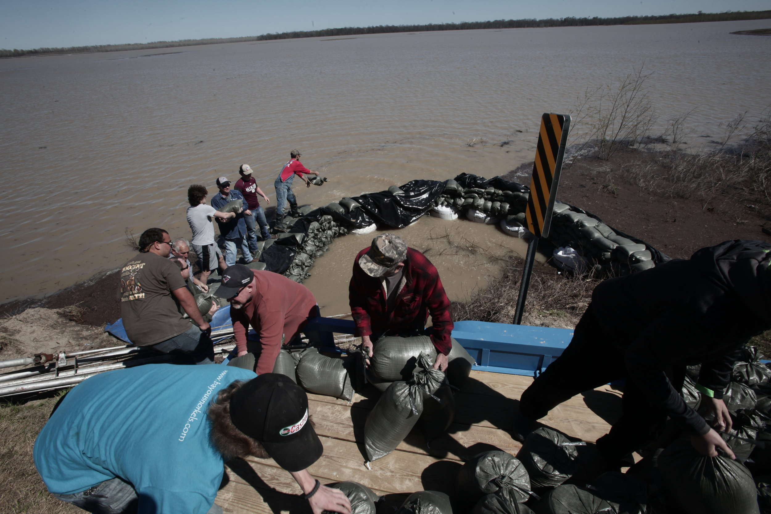 Volunteers and members of the of the Eagle Lake Volunteer Fire Department work together to make a barrier with sandbags to keep floodwaters from crossing under Highway 465 by culvert Wednesday. (Courtland Wells/The Vicksburg Post)