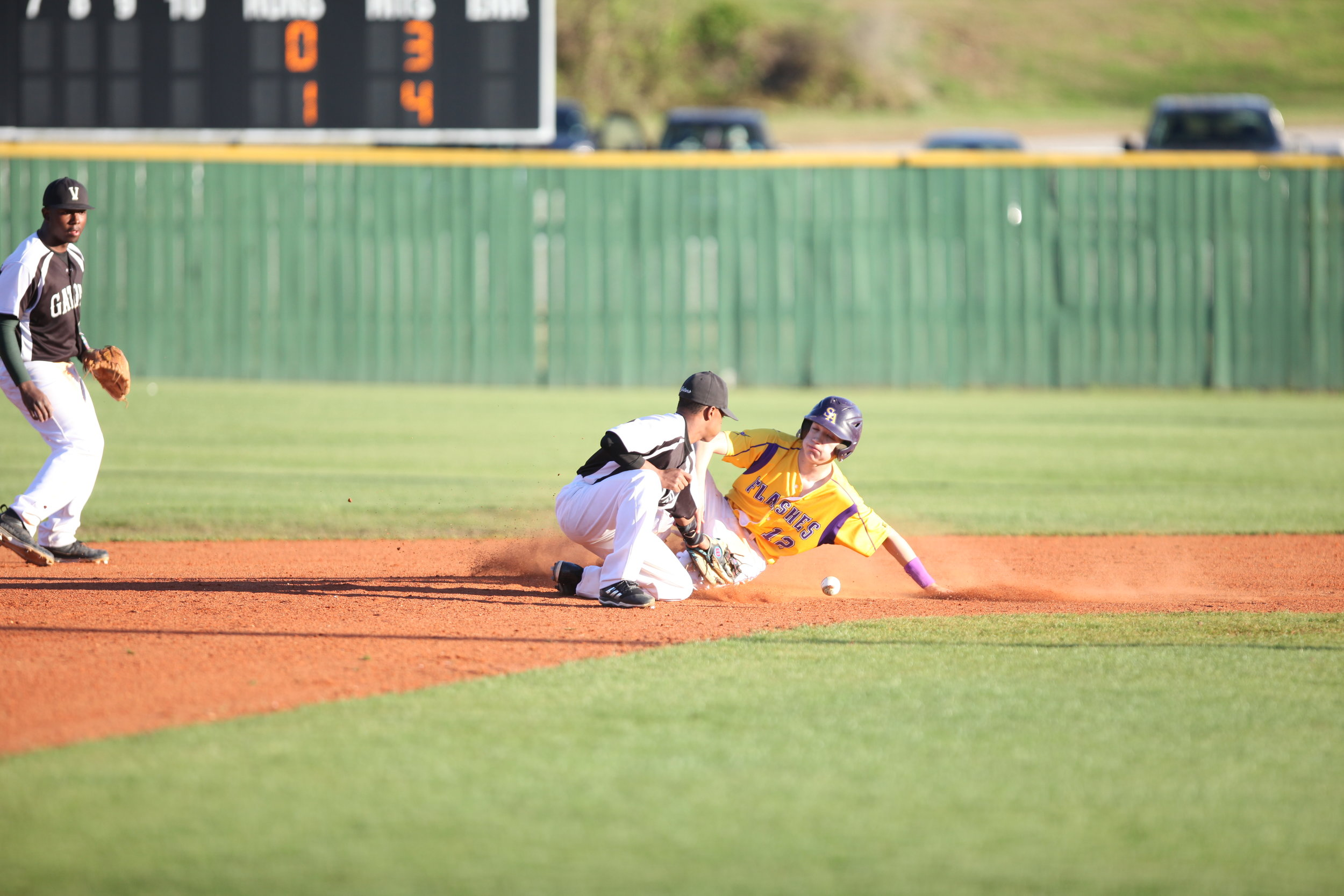 St. Aloysius' Kieran Theriot (12) slides into 2nd base safely as Vicksburg High's Ryan Thompson (11) drops the ball  during the game at Bazinsky Field Wednesday (Courtland Wells/The Vicksburg Post)
