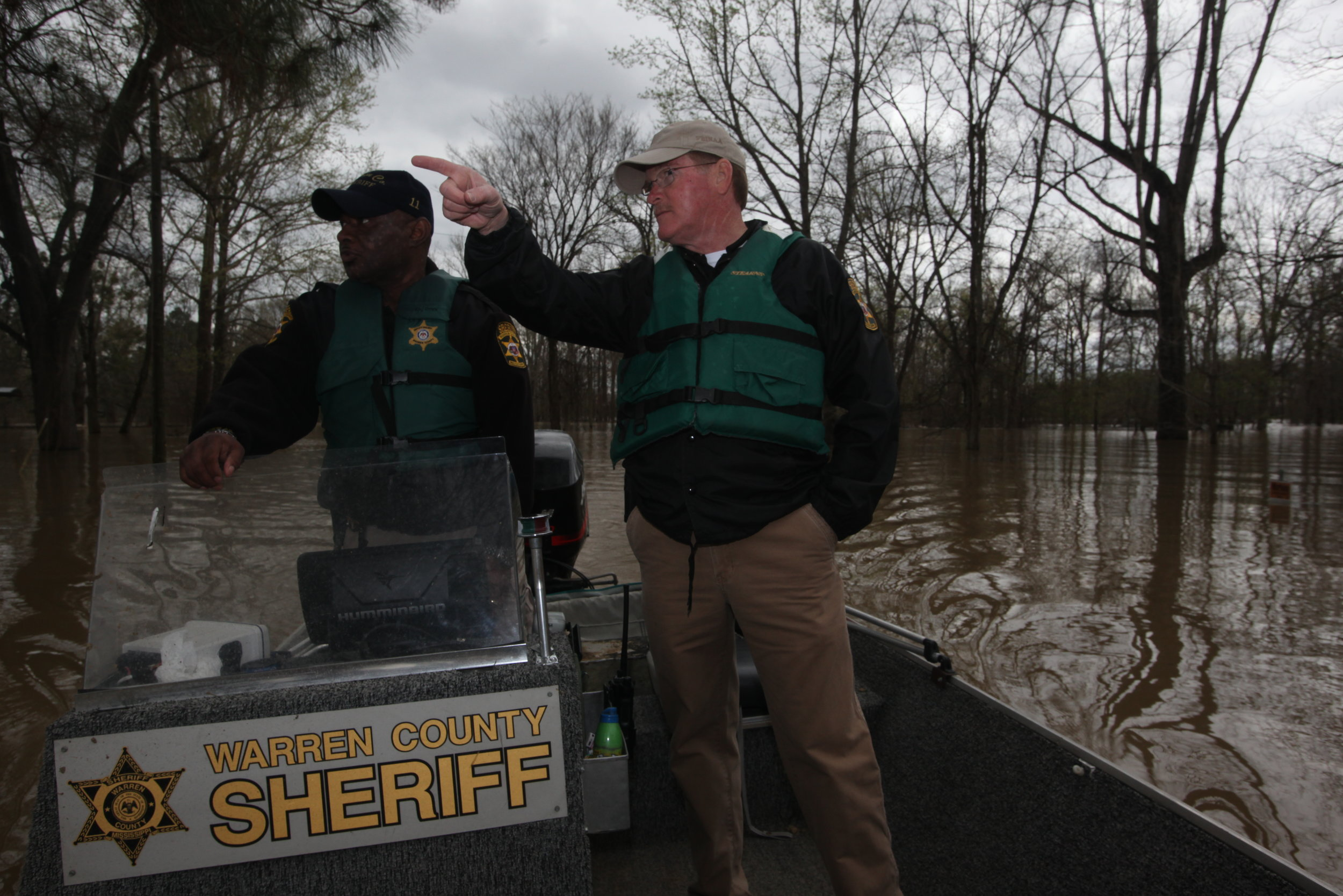 Warren County Sheriff's Detective Sam Winchester steers a boat as Sheriff Martin Pace looks on while patrolling the Chickasaw Subdivision by boat Tuesday. (Courtland Wells/The Vicksburg Post)