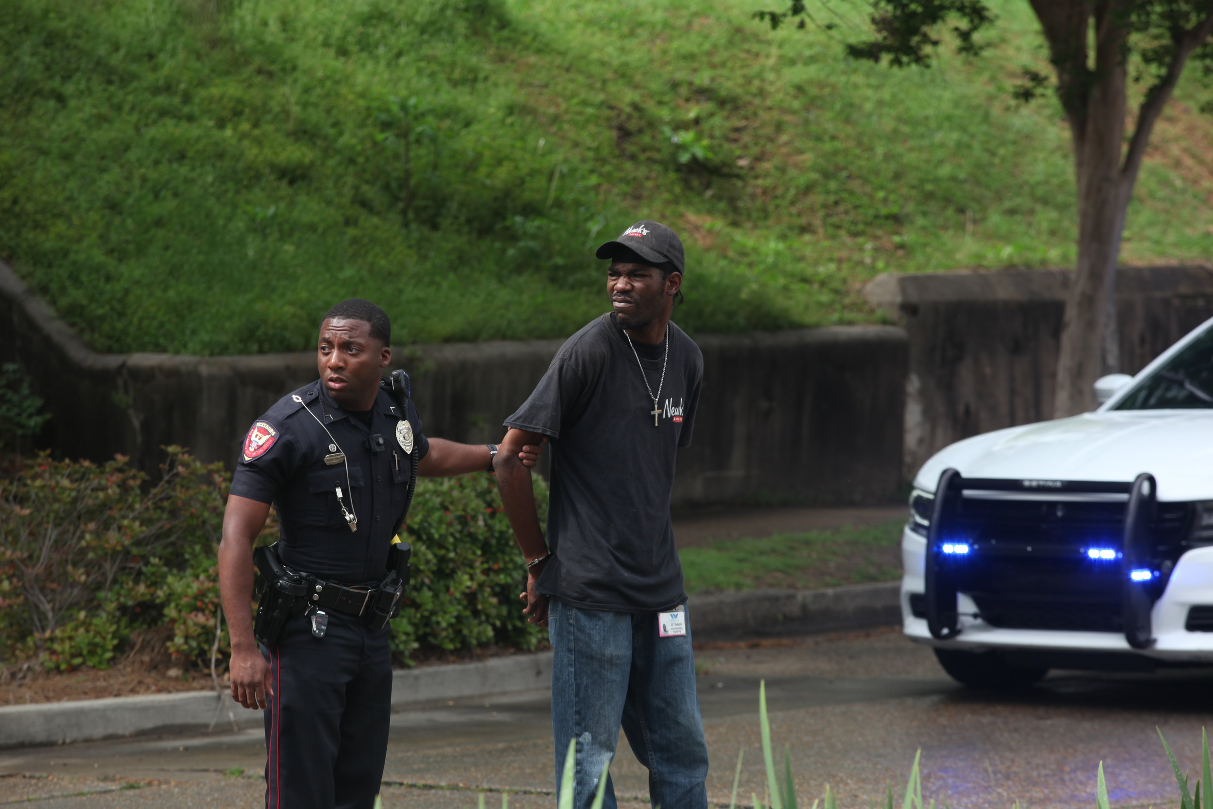 Vicksburg Police Officer Judson Magloire takes Ditanun Demon Simpson, 30, into custody after he allegedly struck a nine-year-old 2nd-grade Dana Road Elementary student with a vehicle after she exited a school bus in front of Vicksburg Fire Department Station 7 located at 3217  Washington Street just around 3:10 p.m. in Vicksburg, Miss., Wednesday, March 28, 2018. The victim was transported to Merit Health River Region with unknown injuries. Simpson is currently charged with reckless driving, no operators license and no proof of insurance (Courtland Wells/The Vicksburg Post, via AP)