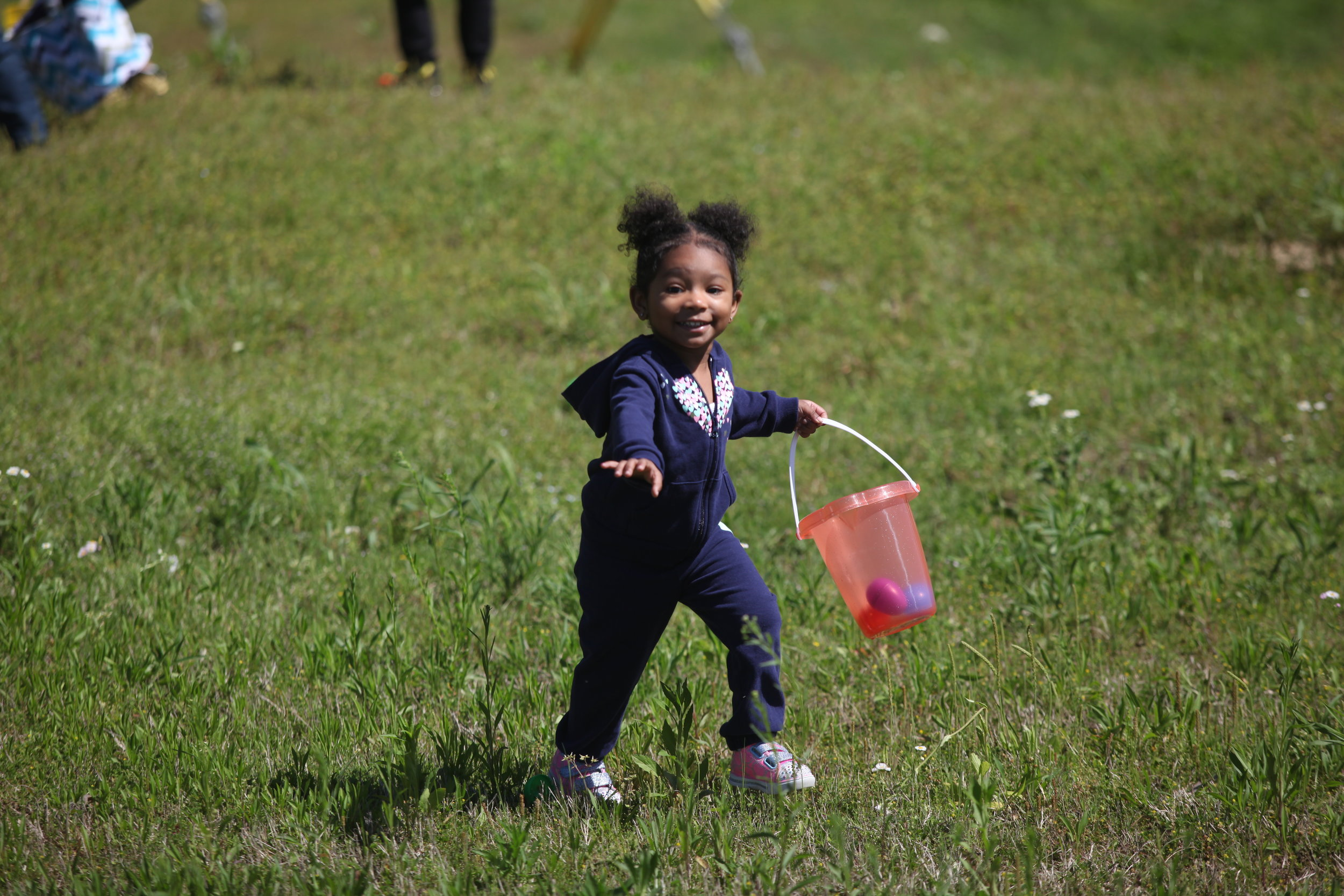 Jaliyah Miles, 2, runs while looking for Easter eggs during the Financial Literacy Easter Egg Hunt by the Academy at King Solomon Baptist Church Saturday. Kids found eggs which they turned in to receive money by color code. The Academy had $5000 for kids to receive for the eggs found. (Courtland Wells/The Vicksburg Post)