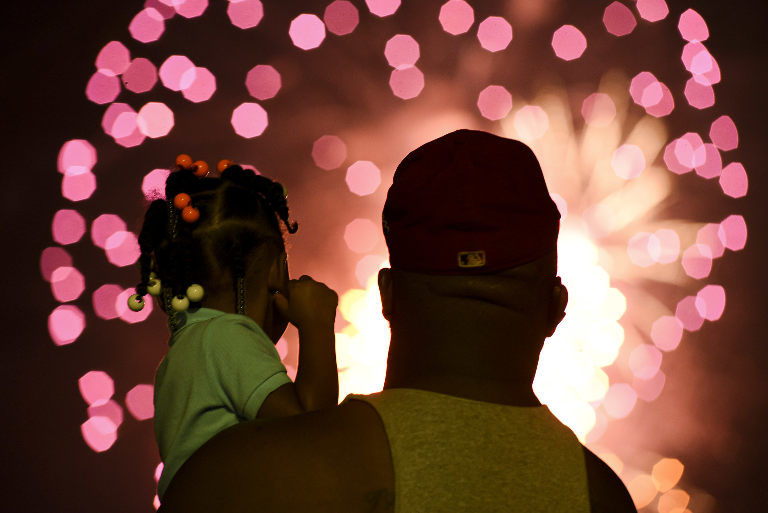 Cedric Johnson holds his goddaughter Miracle Crawley, 2, as fireworks light up the sky during the Fourth of July Fireworks Show at the Vicksburg Riverfront in Vicksburg, Miss., Thursday, July, 4, 2019 (Courtland Wells/The Vicksburg Post via AP)